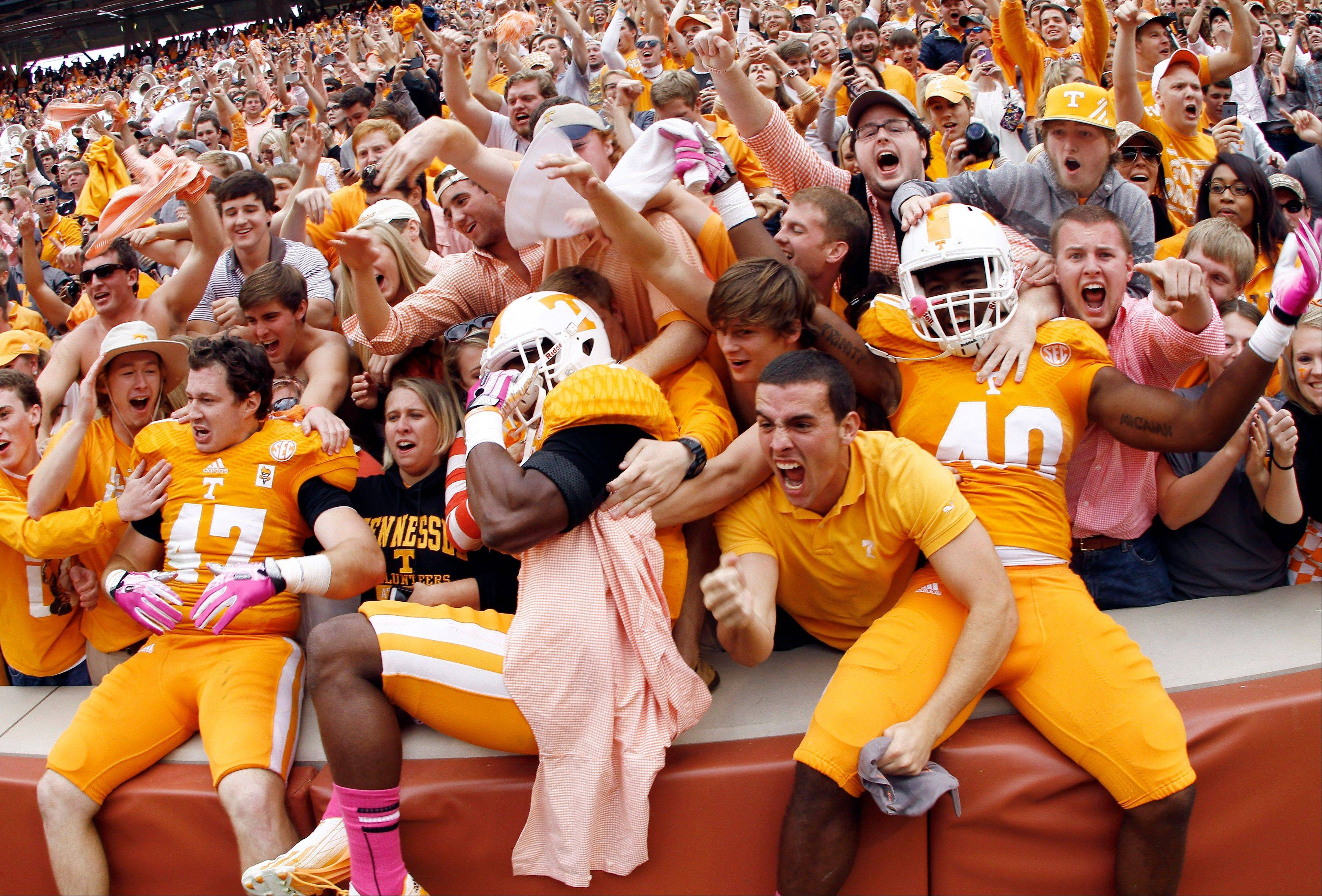 Tennessee linebacker Raiques Crump (40), defensive back Michael F. Williams, center, and linebacker John Propst (47) celebrate with fans after their 23-21 victory over South Carolina.