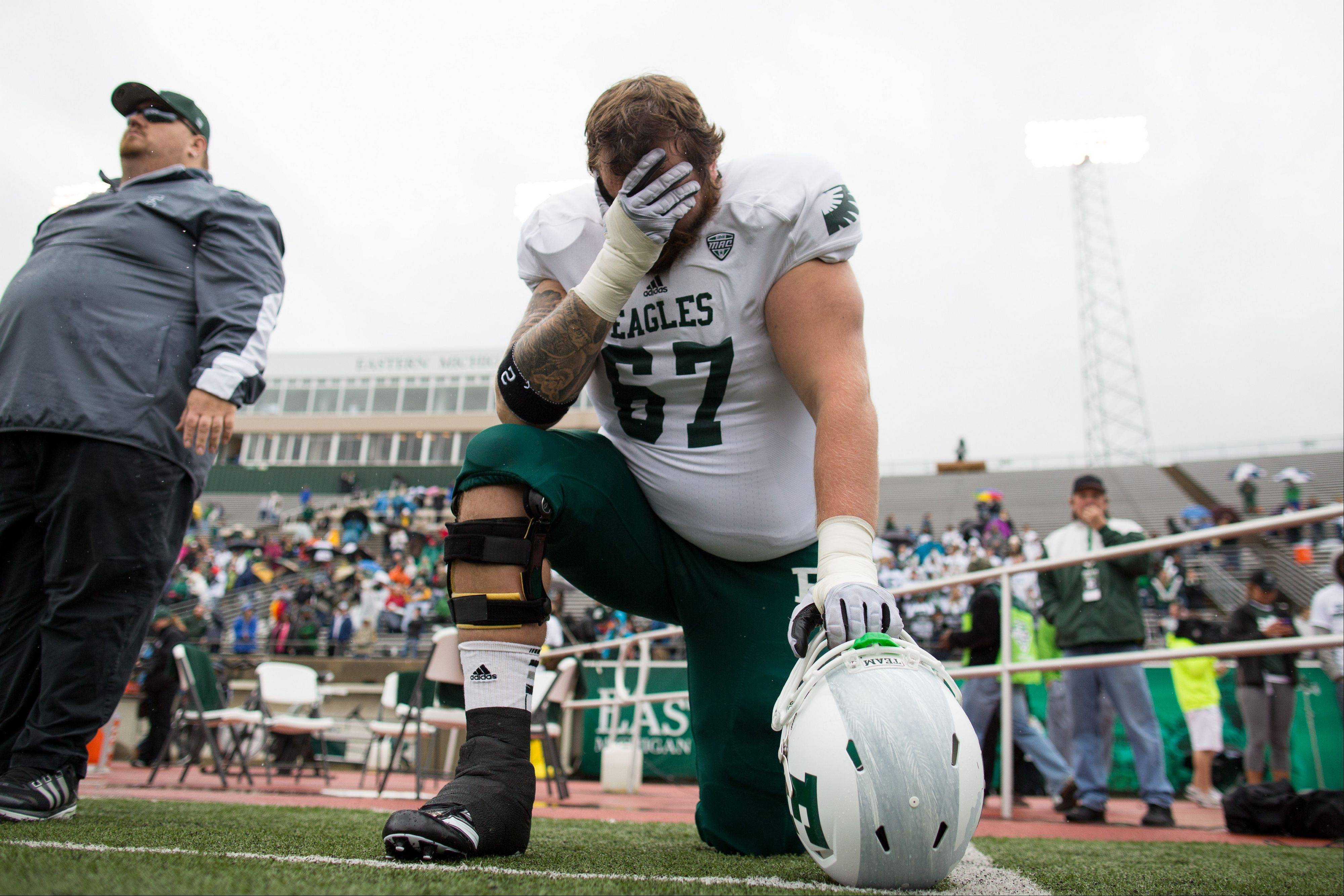 Eastern Michigan University's Campbell Allison knees after a moment of silence to honor Demarius Reed.