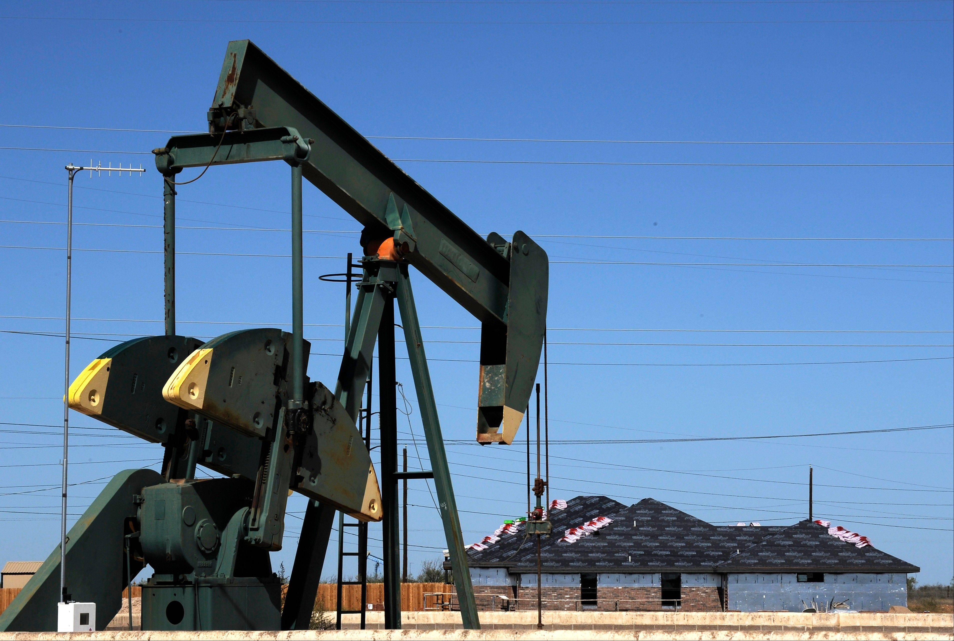 A pump jack works beside the site of new home construction in Midland, Texas. The West Texas town is in the middle of an oil boom with thousands of workers in need of housing.