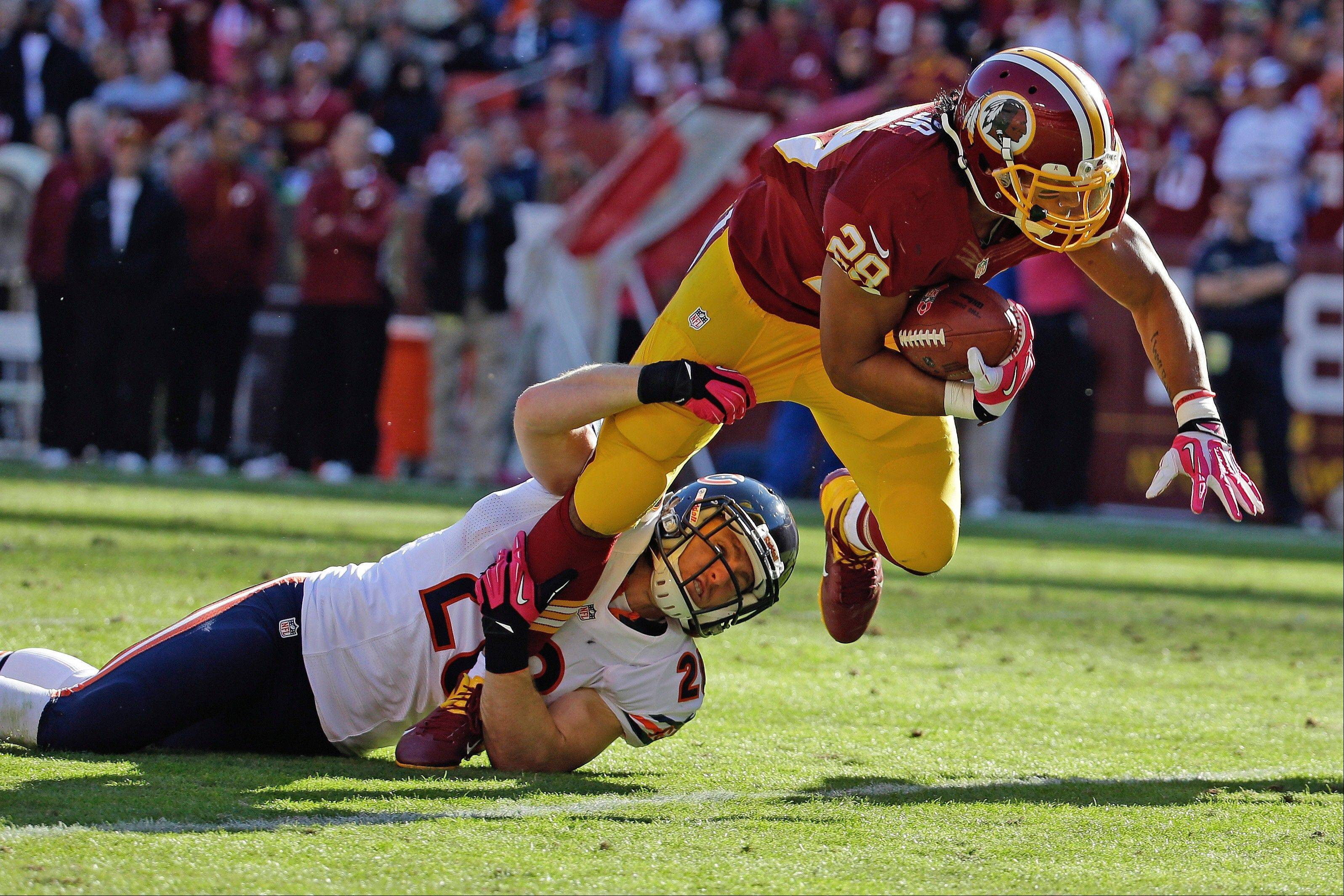 Washington�s Roy Helu, right, is dragged to the turf by the Bears� Craig Steltz, left, in Sunday�s second half.