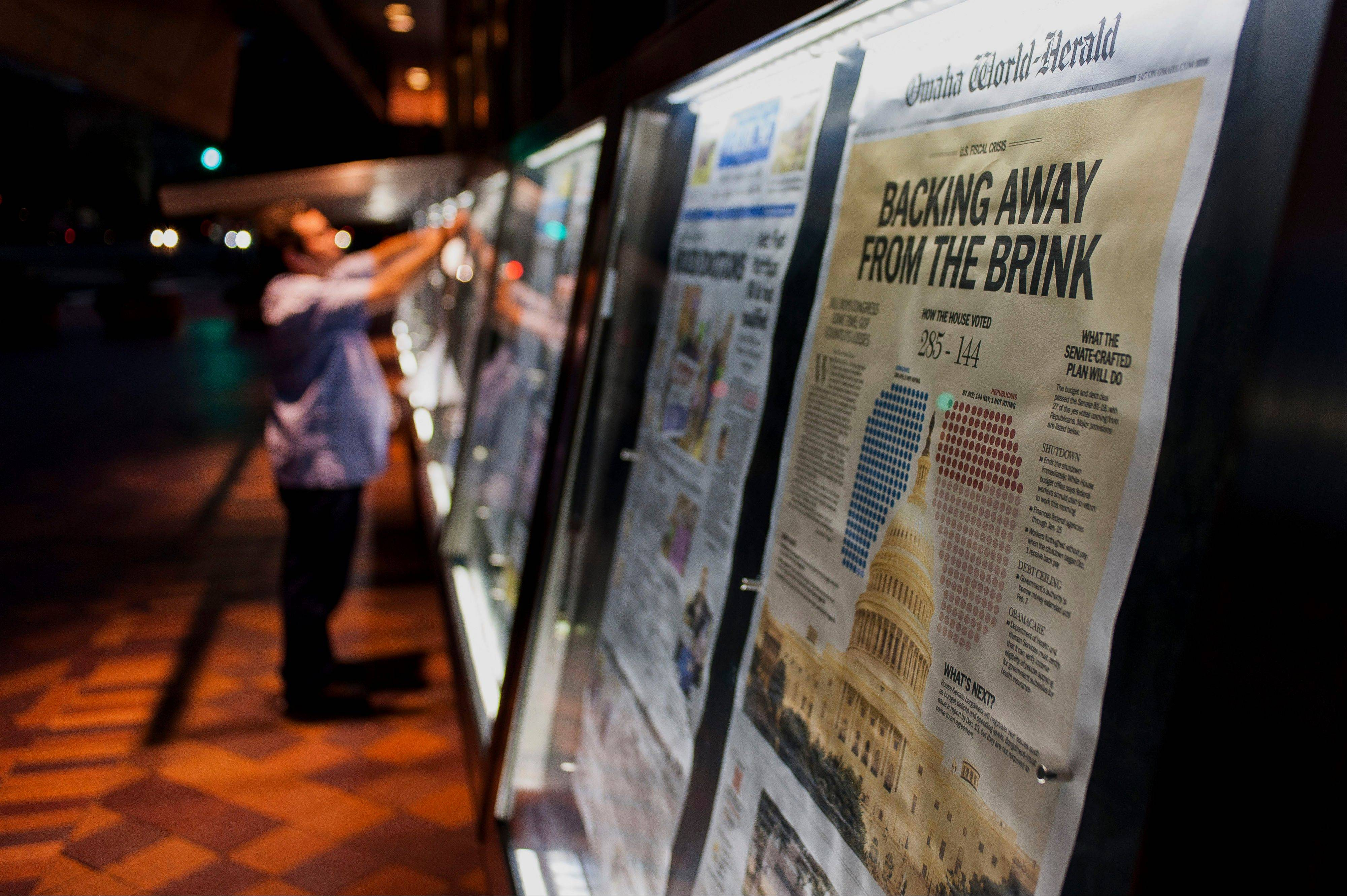 An employee puts front pages in the displays in front of the Newseum in Washington, D.C., on Thursday. On Wednesday night the Congress sent President Obama a bill to avoid government default on its obligations.