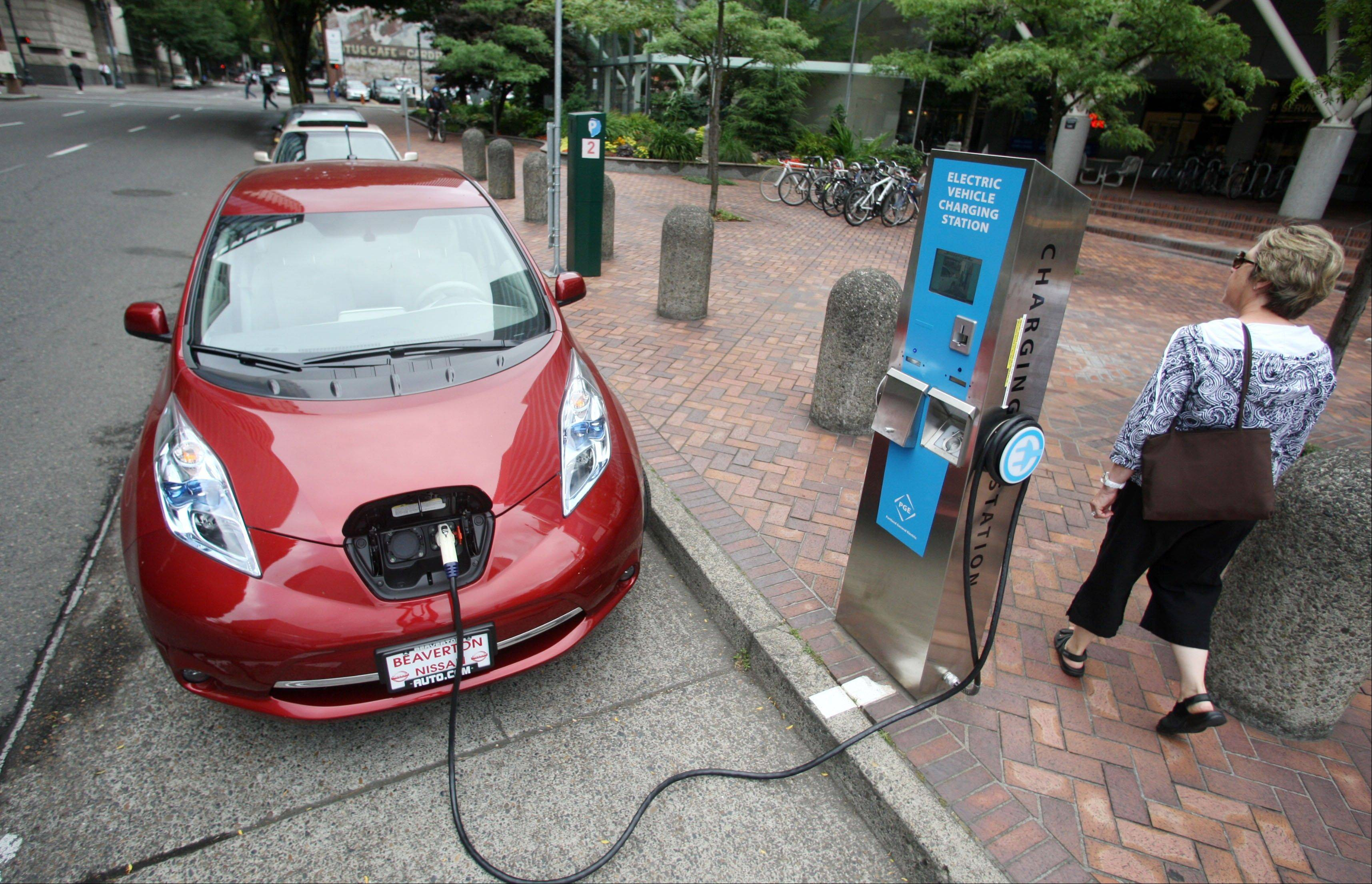 A Nissan Leaf charges at an electric vehicle charging station in Portland, Ore. Automakers have sweetened deals in recent months for plug-in electric cars in a bid to boost sales and move the vehicles off dealer lots as the end of the year nears. Earlier in 2013, Nissan dropped the price of its electric Leaf, helping boost its sales. It's now offering a three-year lease at $199 a month.