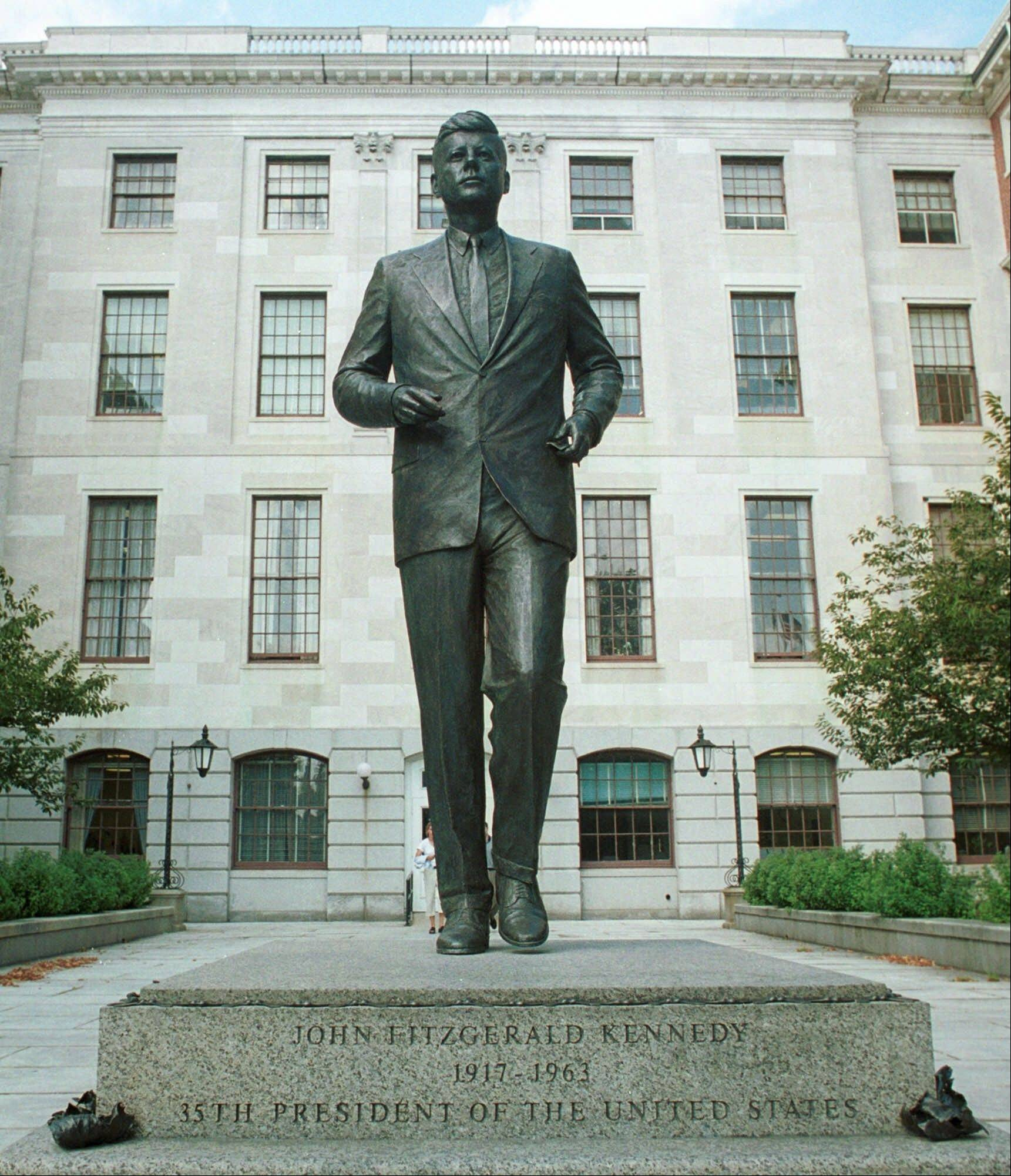 A memorial statue of President John F. Kennedy stands on the grounds of the Massachusetts Statehouse in Boston, which is one of three cities that loom large in the life and death of John F. Kennedy.