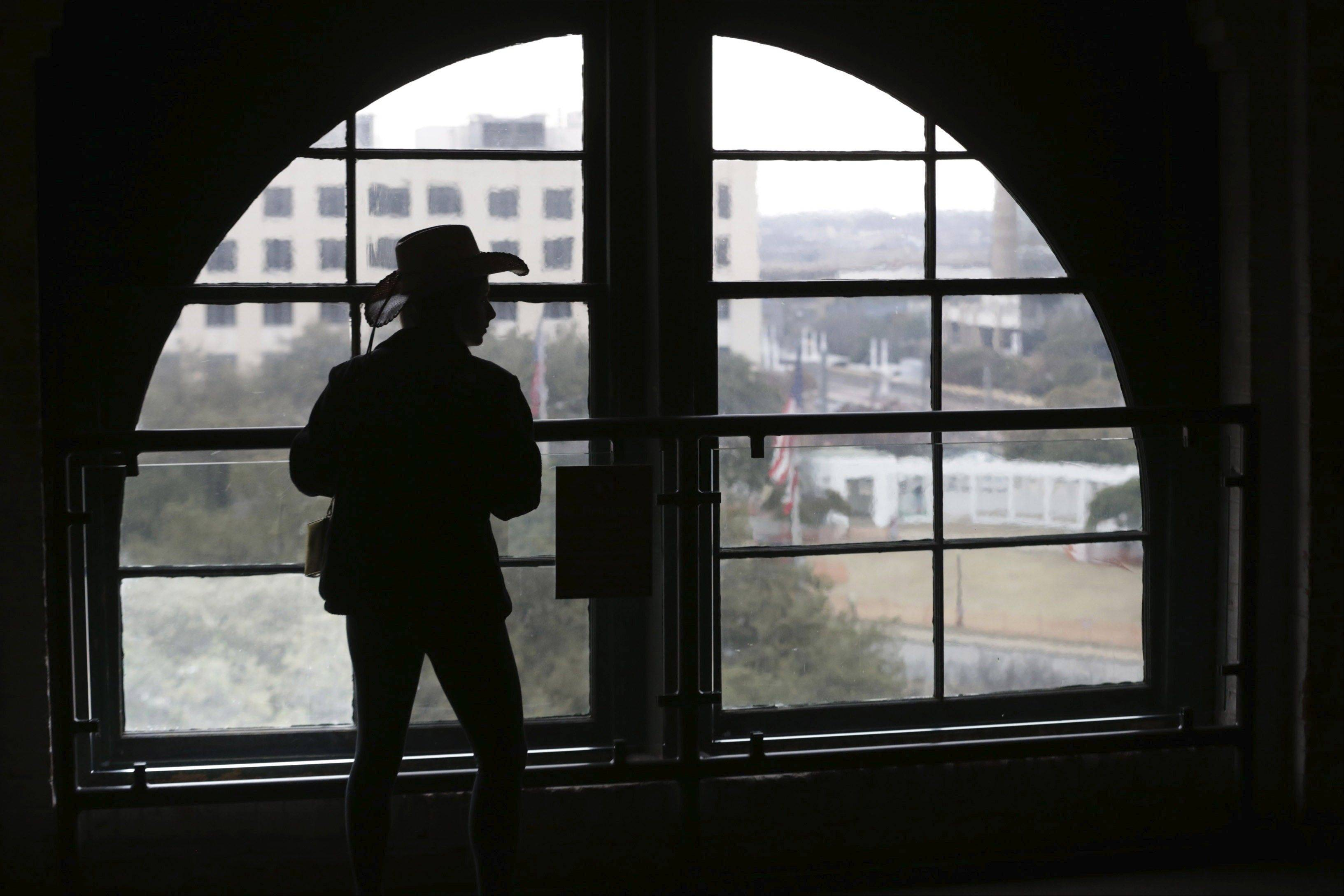 A visitor looks out onto Dealey Plaza from the Sixth Floor Museum located in the former Texas School Book Depository building in Dallas. President John F. Kennedy's assassin Lee Harvey Oswald fired at the president's motorcade from a window on the sixth floor of the Texas School Book Depository on Nov. 22, 1963.