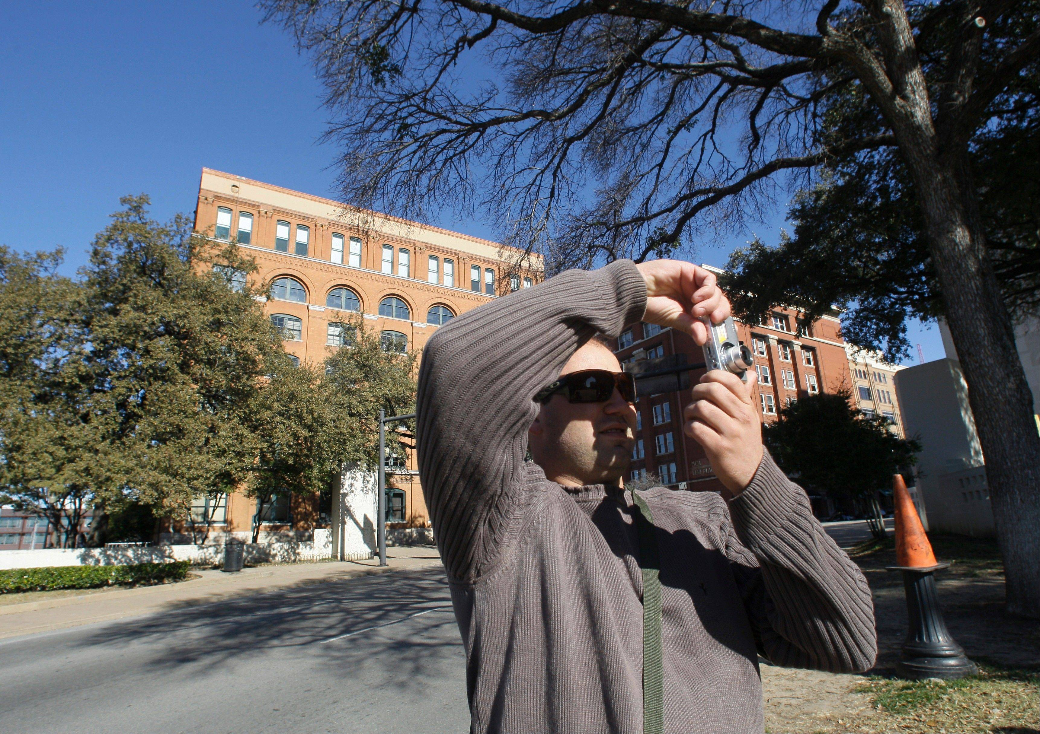 Rafael Boff, of Brazil, takes photographs while visiting Dealey Plaza, site of President John F. Kennedy's assassination, in Dallas. The building once used as a book depository can be seen in the background.