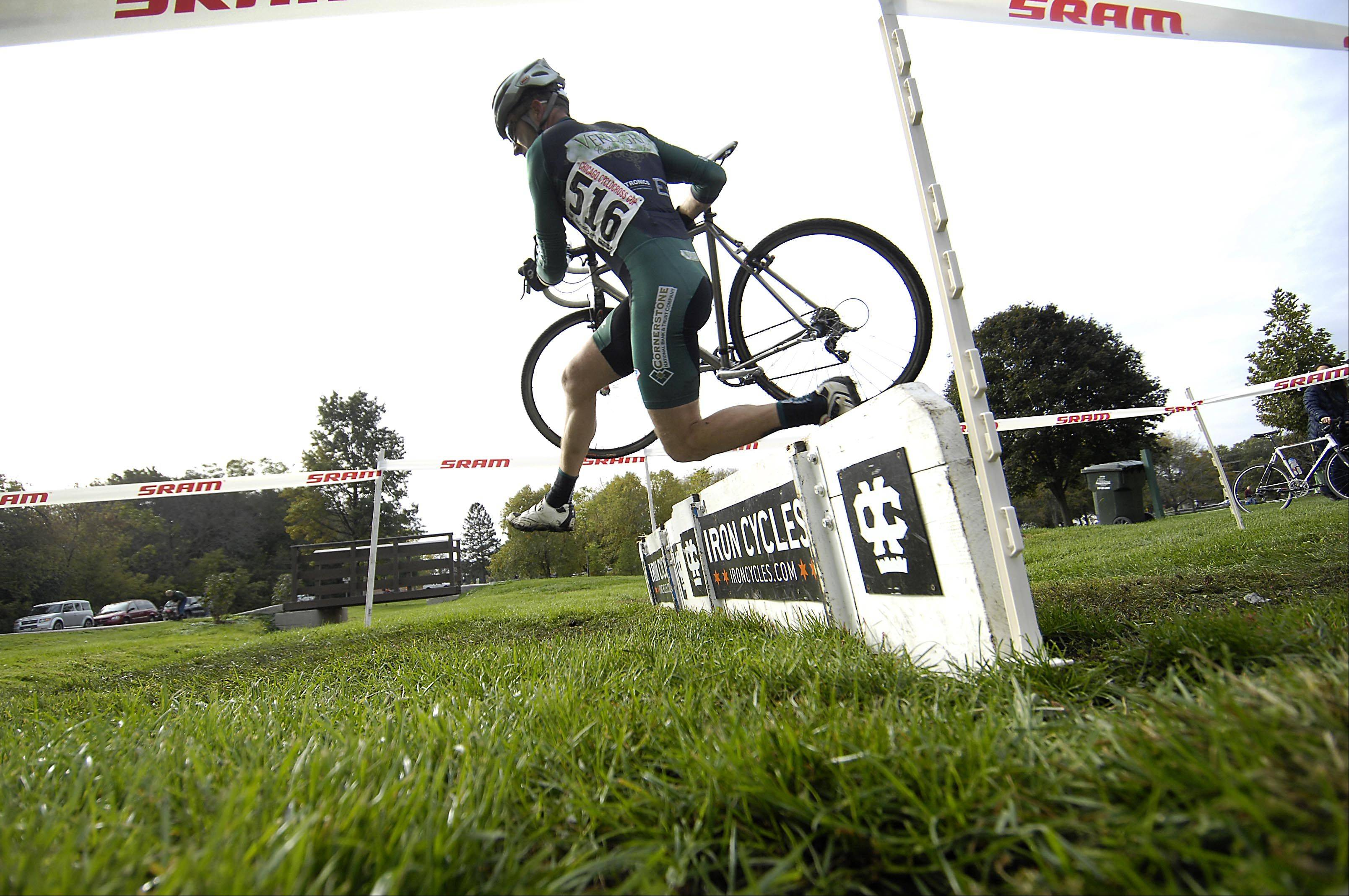 Brian Dougherty, 41, of Elgin, leaps over an obstacle Sunday at the Chicago Cyclocross Cup bicycle races at Carpenter Park in Carpentersville. Hundreds of racers competed in the off-road event.