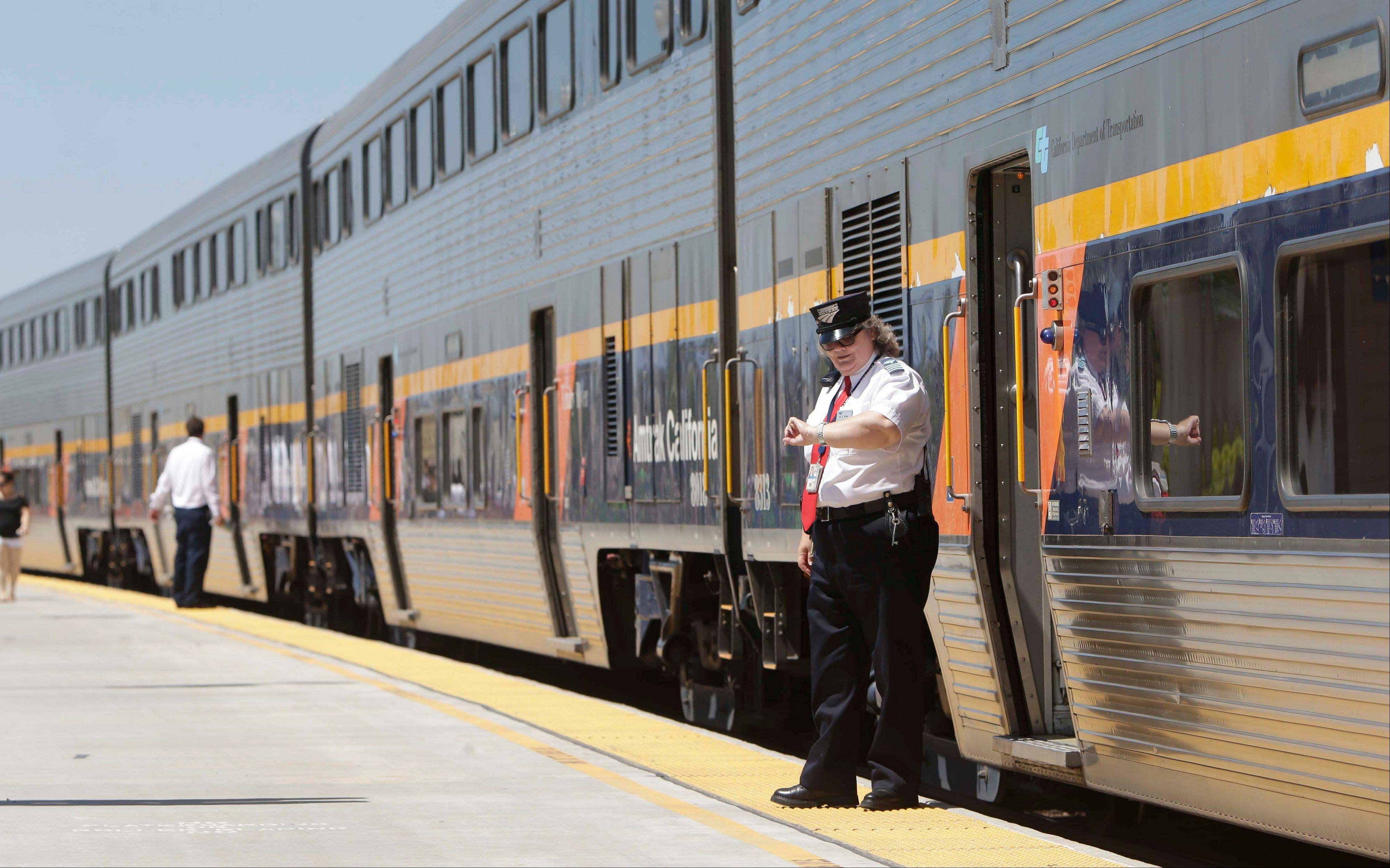 An Amtrak conductor checks the time as the passenger train takes on passengers in Hanford, Calif. The state's plan to build the first high-speed rail system in the nation is intended to alleviate gridlock, connect the Central Valley to better jobs and ease pollution, but many residents oppose the $68 billion project.