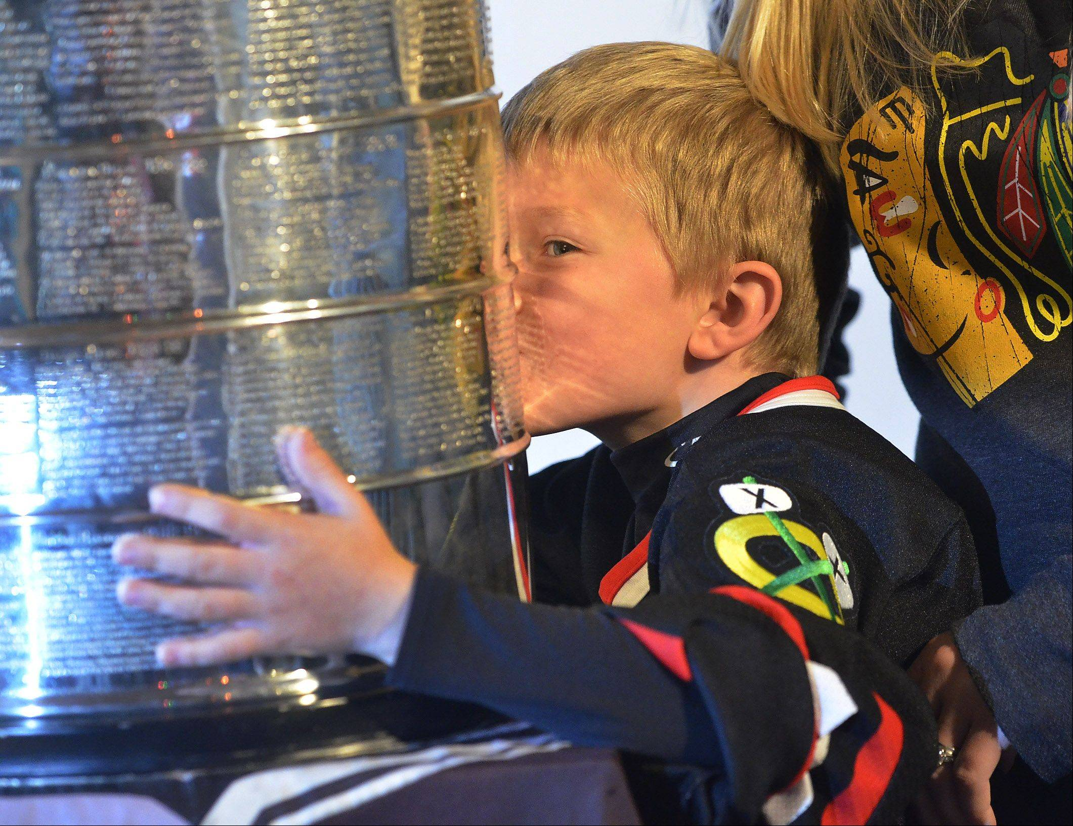 Jacob Thorby, of Schaumburg, gives a smooch to the Stanley Cup on display at the Trickster Art Gallery in Schaumburg Saturday.