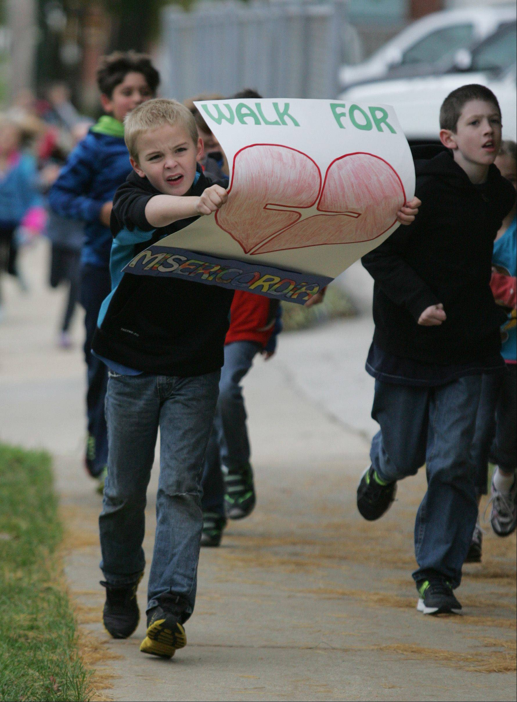 St. Patrick Catholic School third-grader Grant Bettag finds it a bit hard to run full speed and carry a sign during a walk-a-thon Friday in St. Charles to raise money for Misericordia, an organization that supports more than 560 children and adults with developmental disabilities. Students walked, or ran laps, around the school and church campus and raised money from sponsors for each lap they completed.