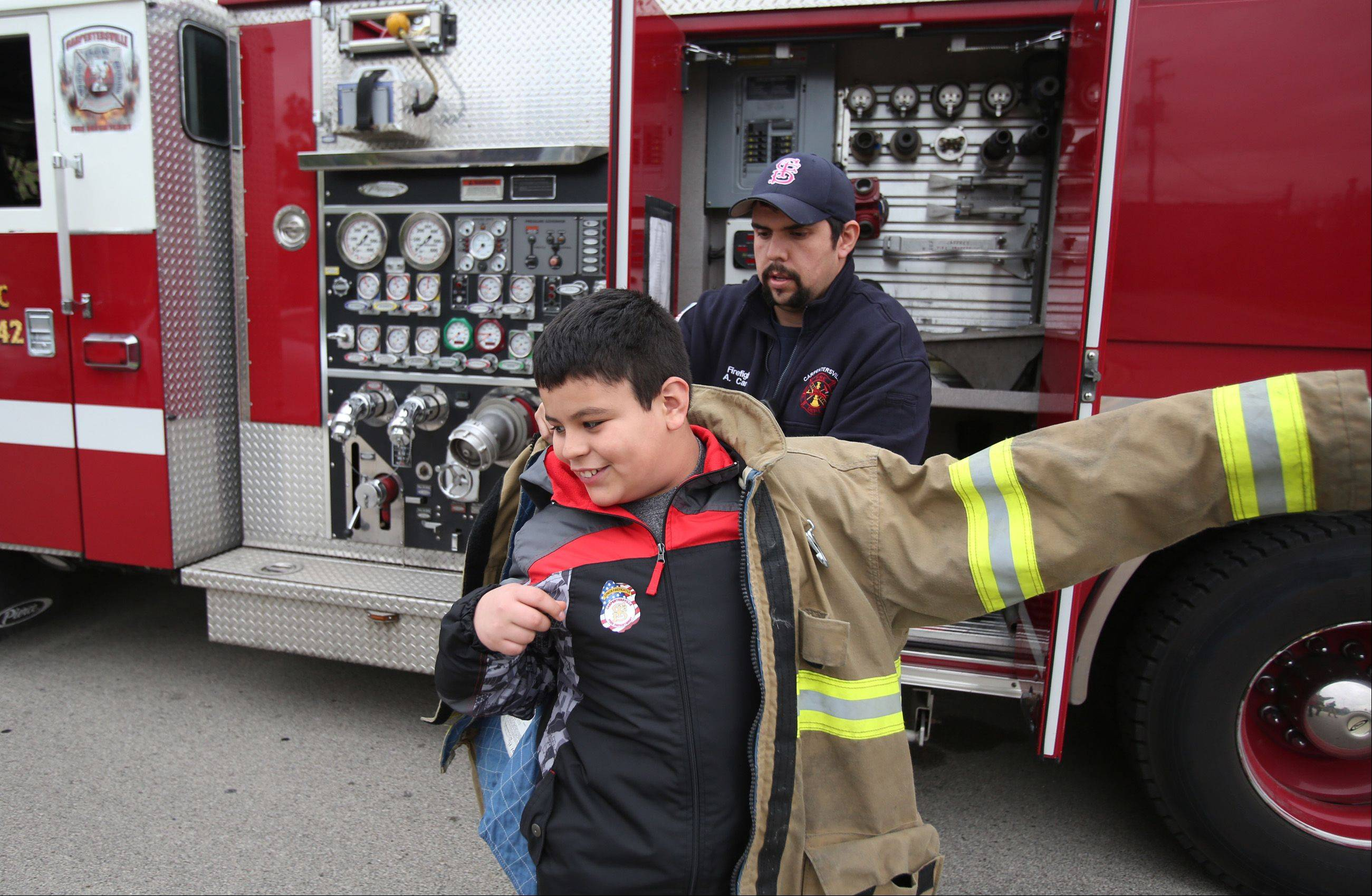 "Lakewood School fifth-grader Julian Garcia Pulida earned enough ""Bulldog Bucks"" through good behavior at school that he earned a ride home aboard a Carpentersville fire engine Friday, along with his friend Fernando Aguilar. Carpentersville firefighter Art Carrillo helps Julian put on a department jacket for his ride home. The ""bucks"" were earned through the school's Positive Behavior Intervention System."