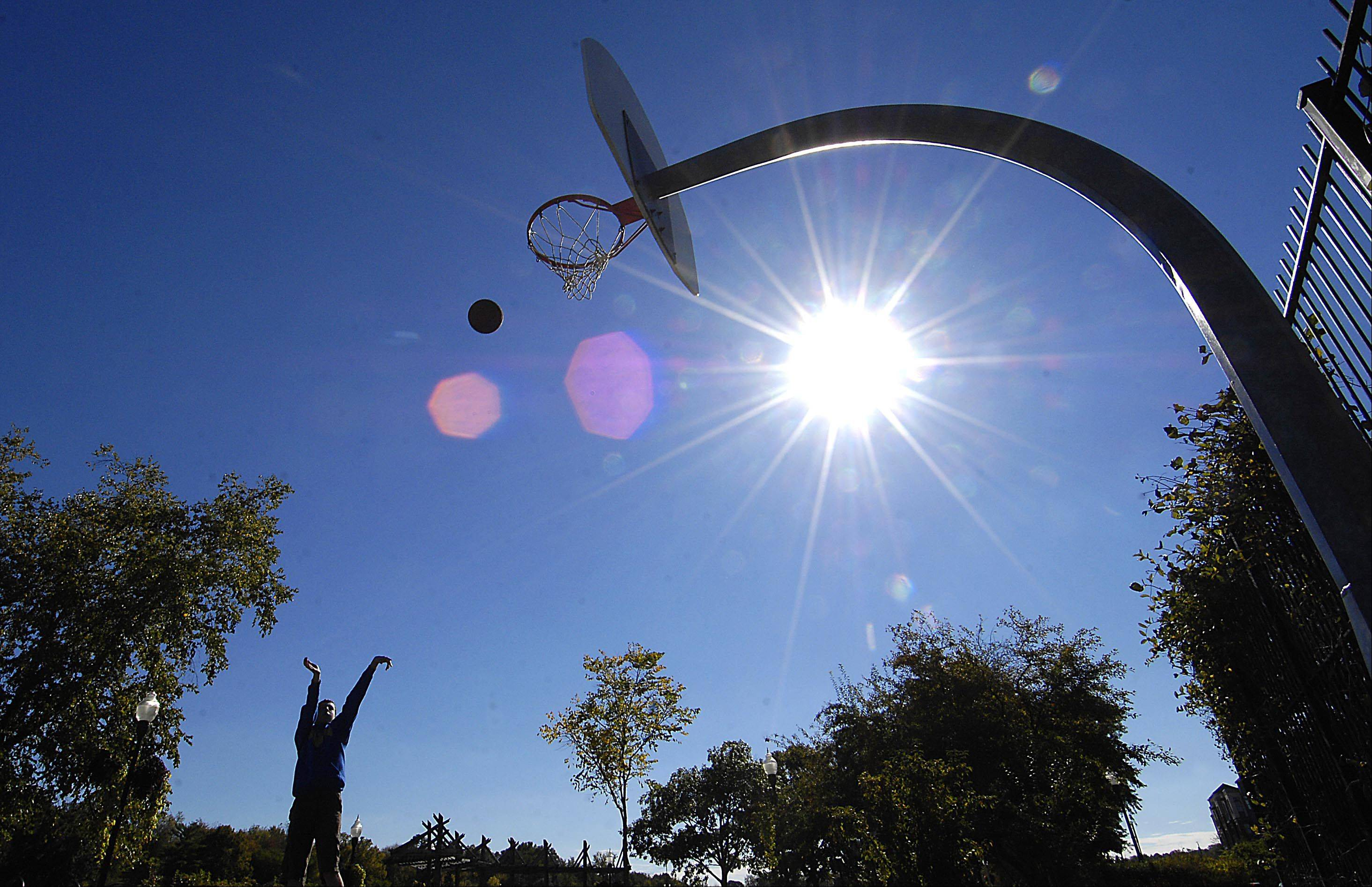 With the day off from school for Columbus Day, Gilbert Green, 14, launches long range basketball shots in River Front Park in Algonquin Monday afternoon. He was visiting with his family from Lake Forest.