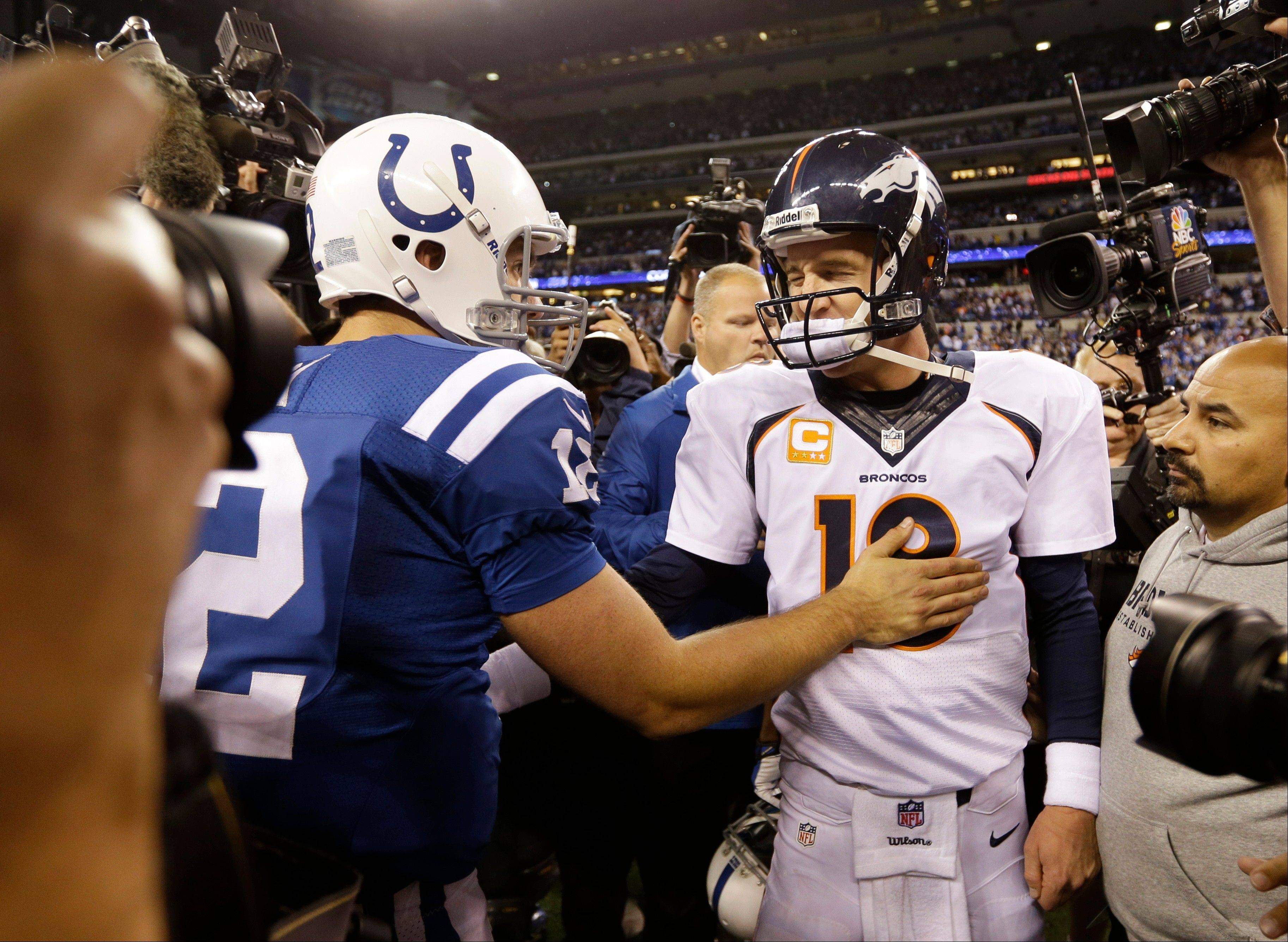 Denver Broncos quarterback Peyton Manning, right, greets Indianapolis Colts quarterback Andrew Luck (12) after an NFL football game, Sunday, Oct. 20, 2013, in Indianapolis. The Colts won 39-33.