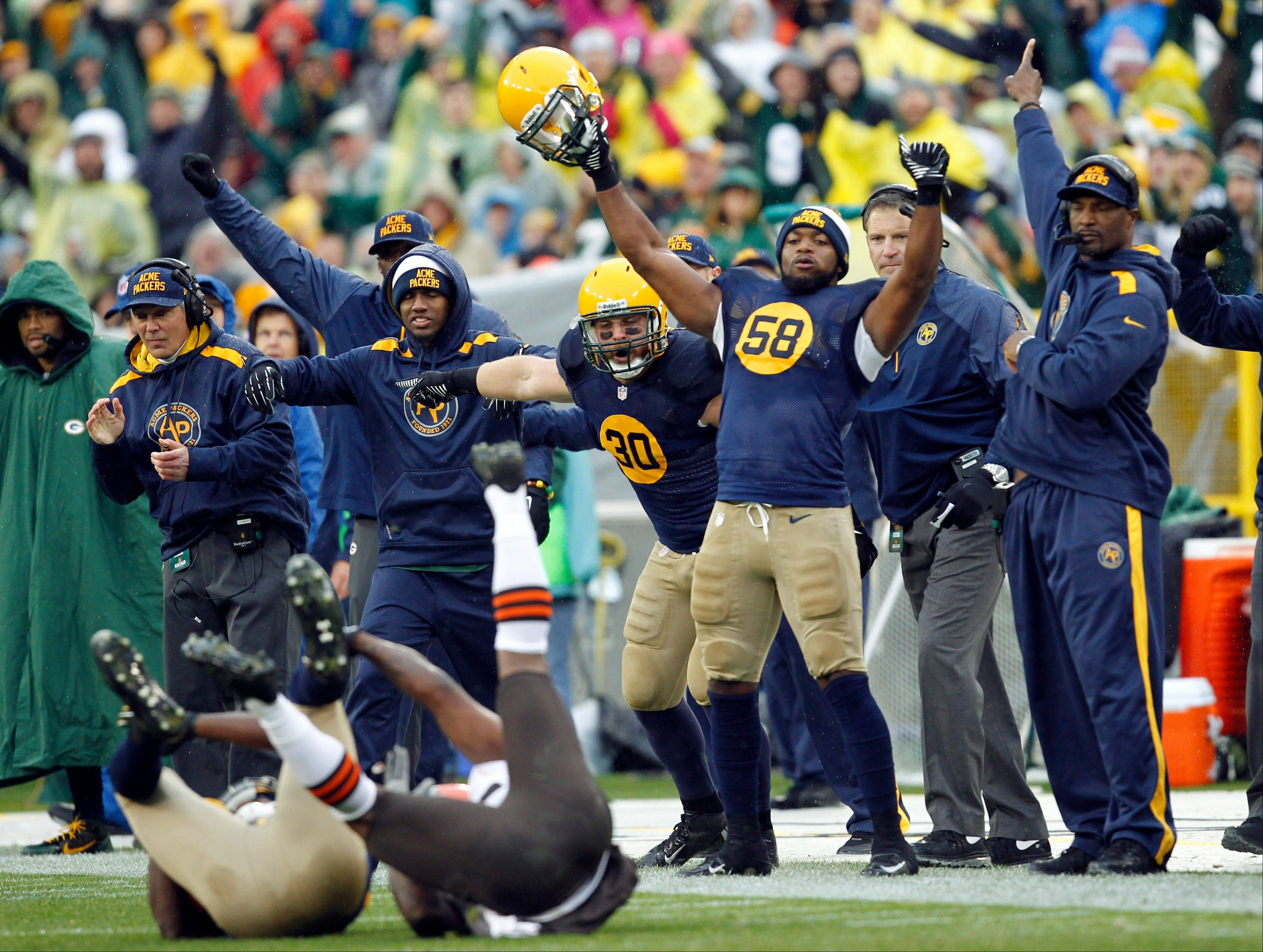 The Green Bay Packers bench celebrates after cornerback Davon House intercepted a pass during the first half of an NFL football game against the Cleveland Browns Sunday, Oct. 20, 2013, in Green Bay, Wis.
