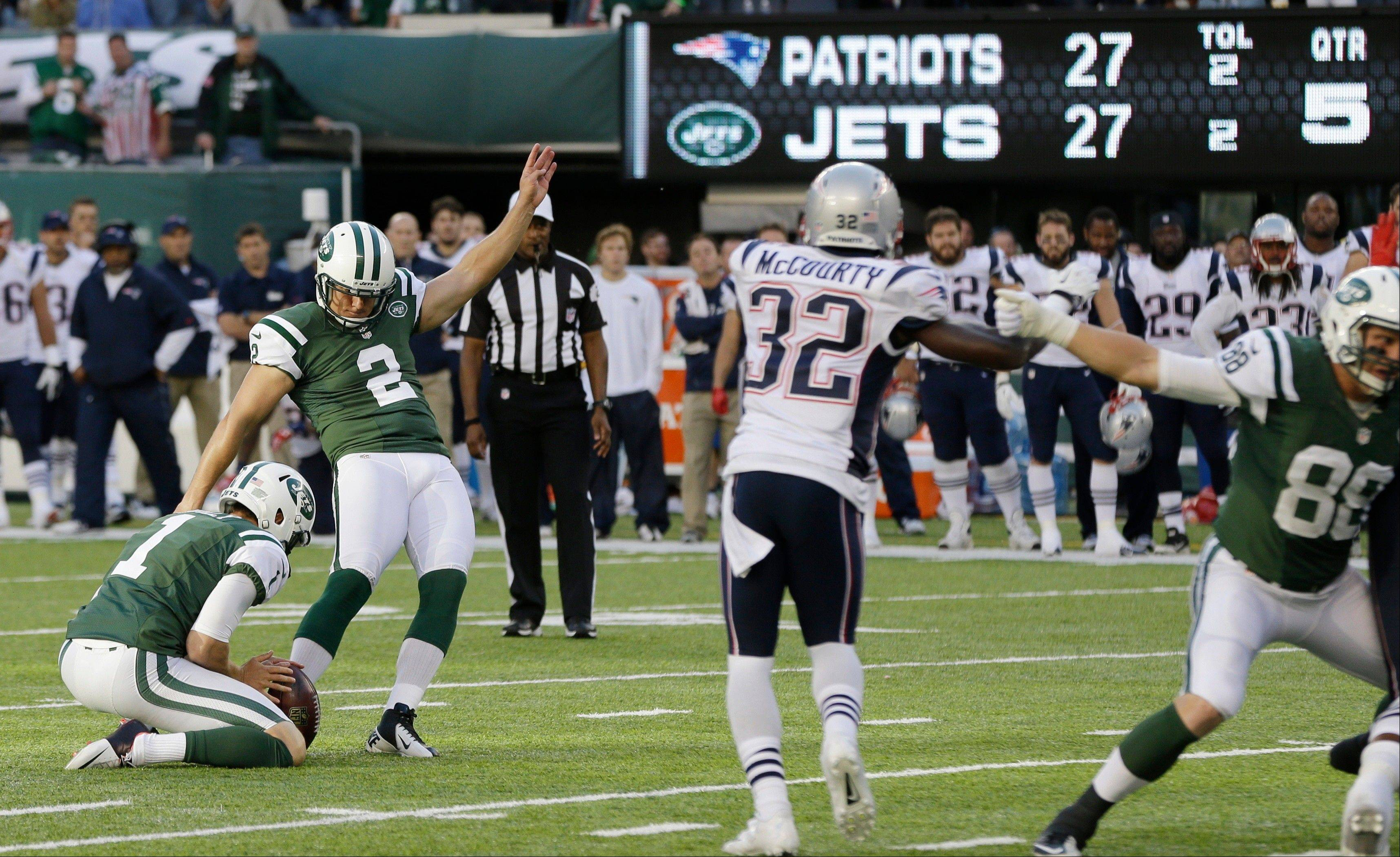 New York Jets kicker Nick Folk (2) kicks a field goal to win the game during overtime of an NFL football game against the New England Patriots Sunday, Oct. 20, 2013 in East Rutherford, N.J. The Jets won the game 30-27. The Patriots' Devin McCourty (32) is at center.
