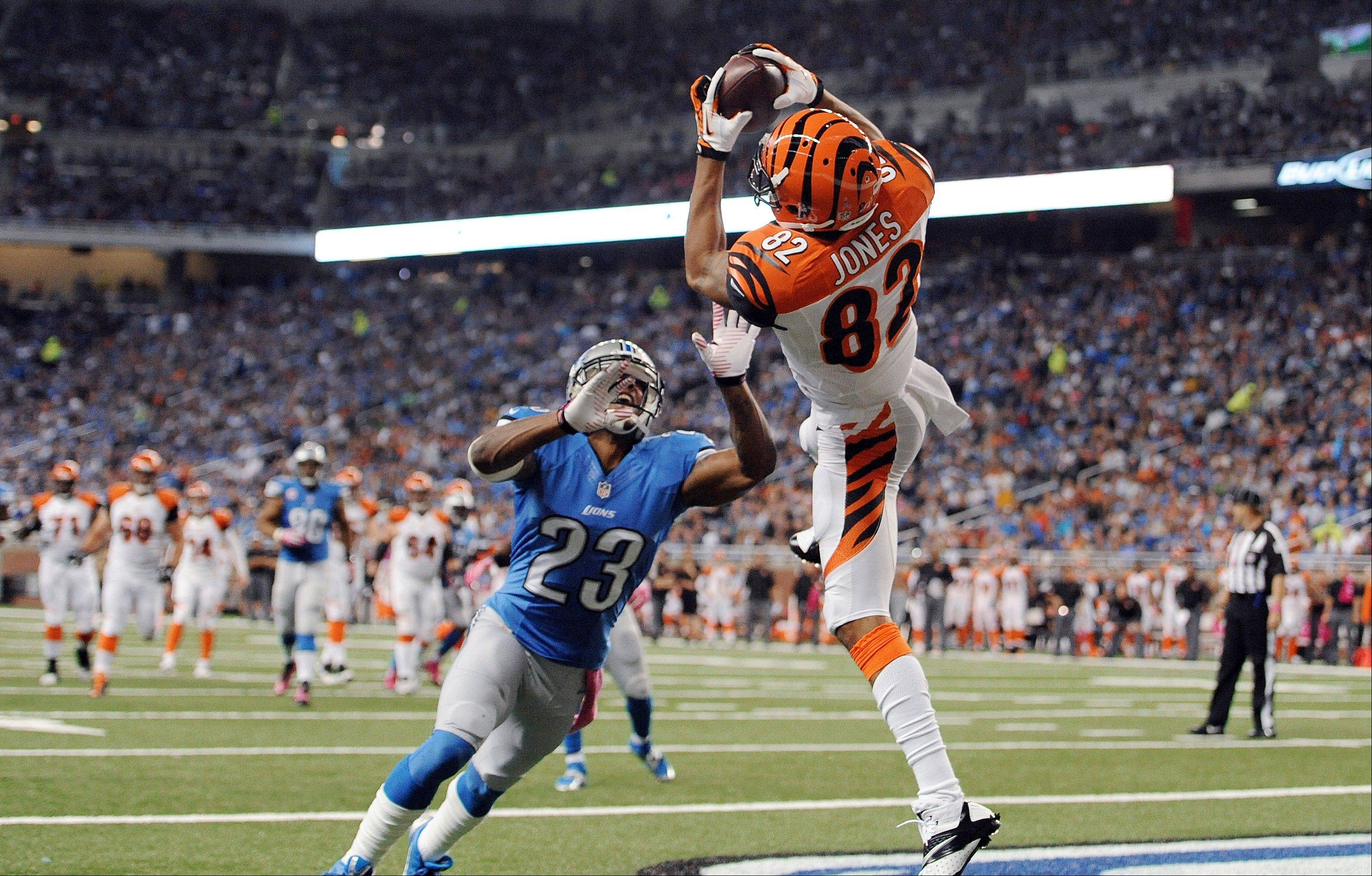 Cincinnati Bengals' Marvin Jones (82) catches a 12-yard touchdown reception as Detroit Lions' Chris Houston (23) defends in the second quarter of an NFL football game on Sunday, Oct. 20, 2013, in Detroit.
