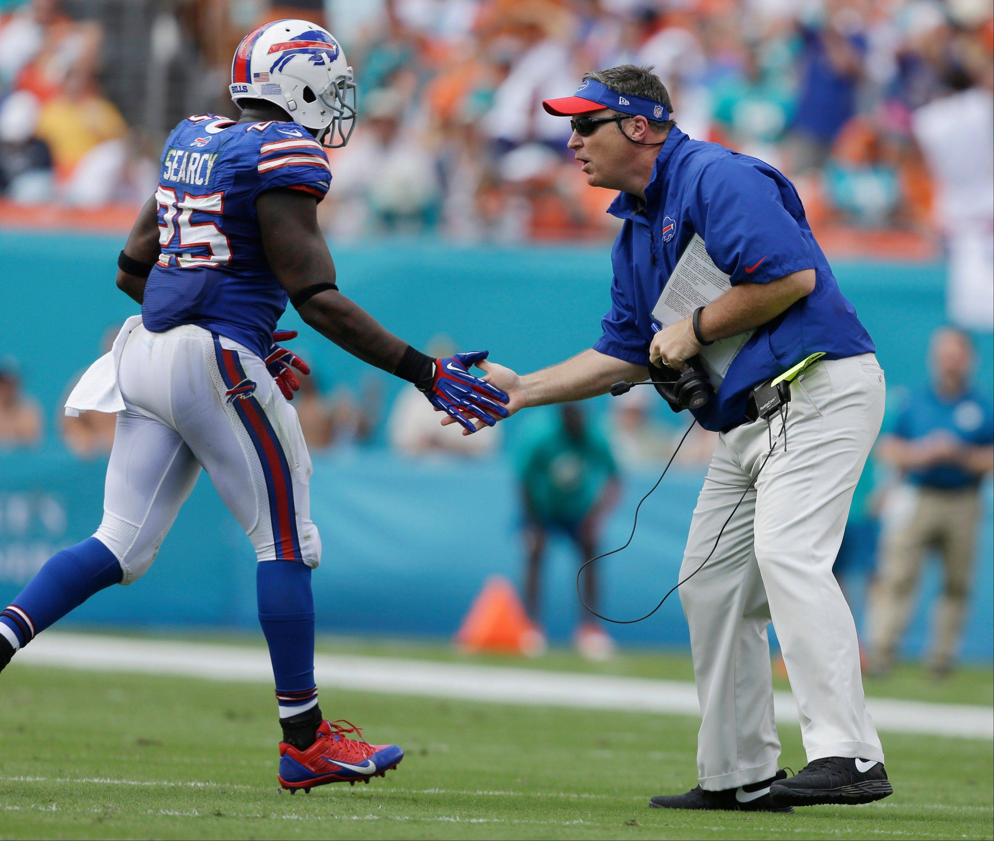 Buffalo Bills head coach Doug Marrone greets Buffalo Bills strong safety Da'Norris Searcy (25) after a play during the first half of an NFL football game against the Miami Dolphins, Sunday, Oct. 20, 2013, in Miami Gardens, Fla.