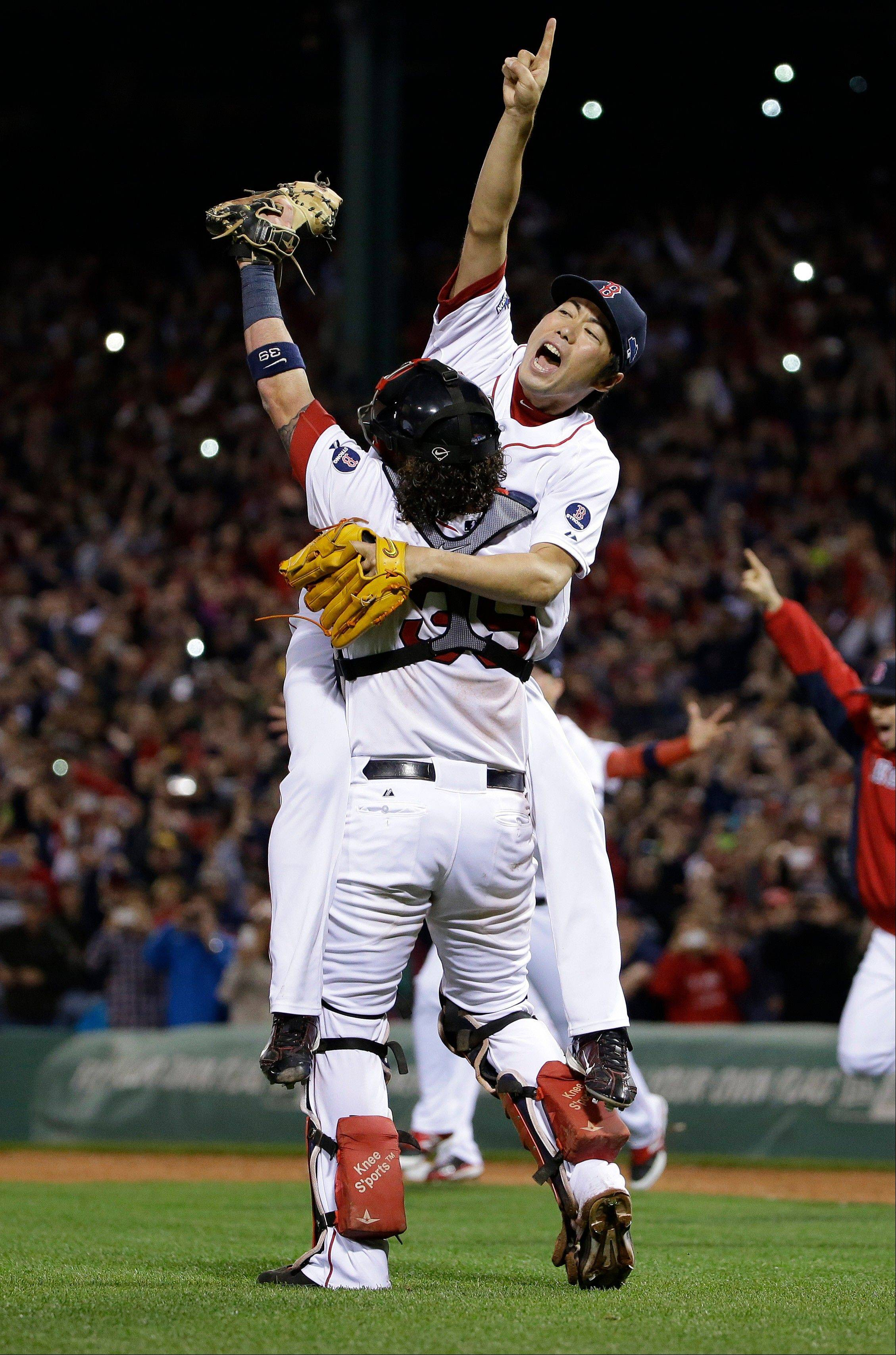 Boston Red Sox relief pitcher Koji Uehara, rear, and catcher Jarrod Saltalamacchia celebrate the Red Sox' 5-2 win over the Detroit Tigers in Game 6 of the American League baseball championship series.