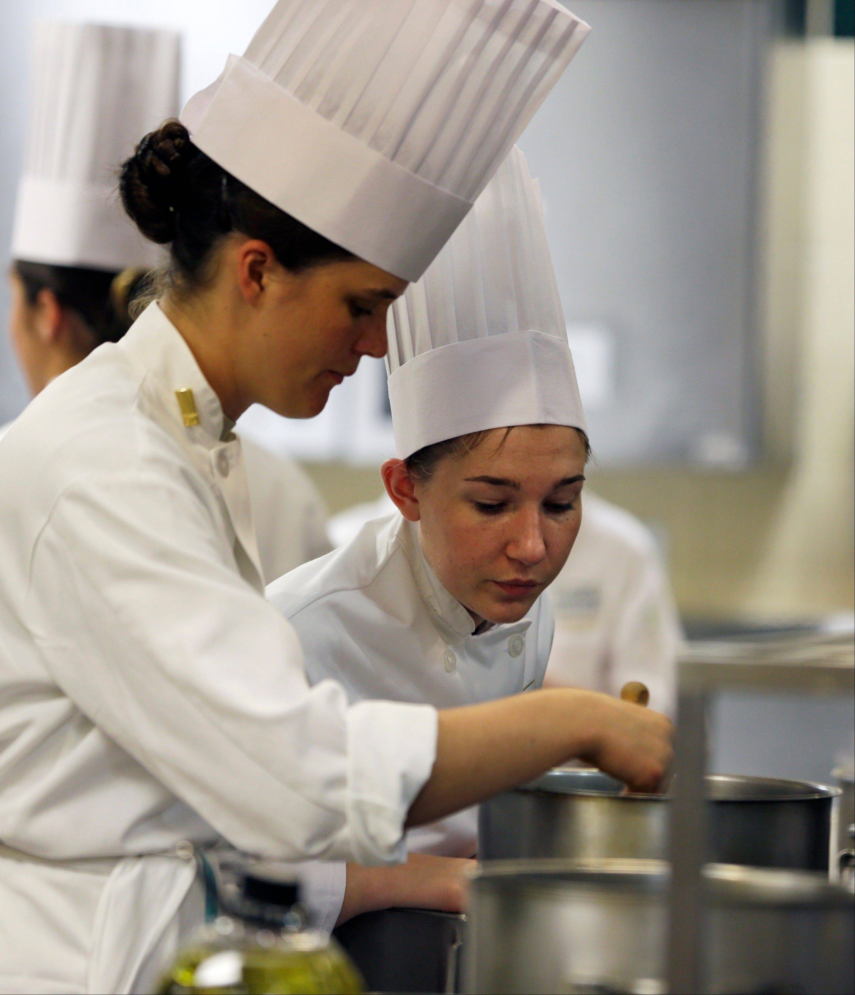 West Point Cadet Erin Mauldin of Albuquerque, N.M., left, and Culinary Institute of America student Clare Wagner of Detroit, work in a kitchen during an exchange program at the New York culinary schoo earlier this month.