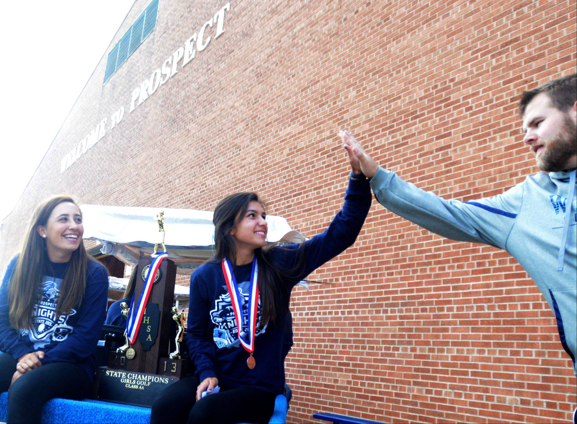Prospect girls varsity golf team members Isabella Flack, left, and Ally Scaccia, center, are congratulated by assistant boys football coach Tim Beishir just before a pep rally celebrating the team's second state championship in three seasons.