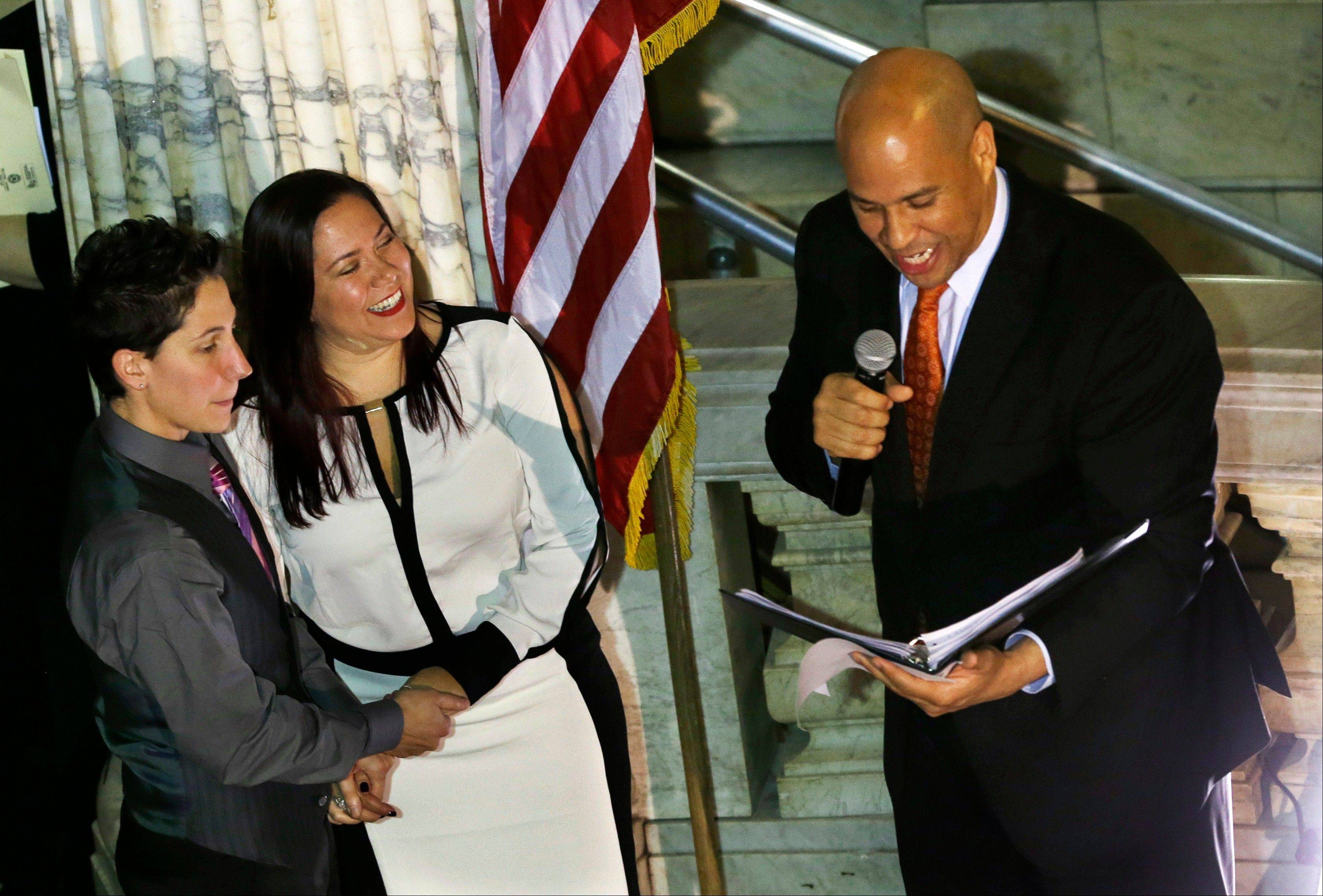 Newark Mayor and Senator-elect Cory Booker, right, officiates the ceremony for the same-sex marriage of Liz Salerno, left, 38, and Gabriela Celeiro, 34, center, at Newark City Hall just after midnight Monday.