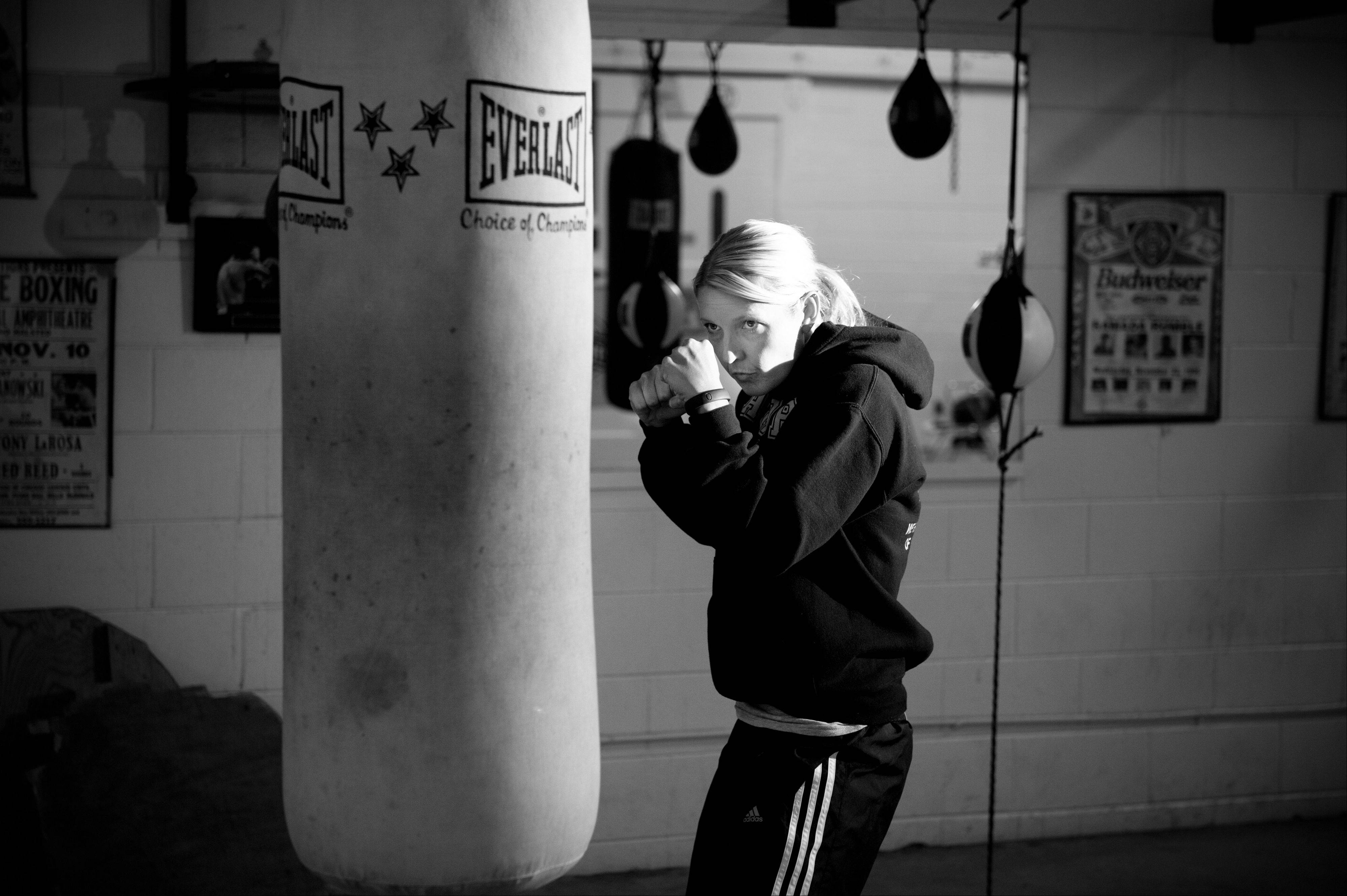 "Aurora Police Cmdr. Kristen Ziman hits the heavy bag at the Jesse ""The Law"" Torres Boxing Club in Aurora while training for Sunday's charity boxing event."