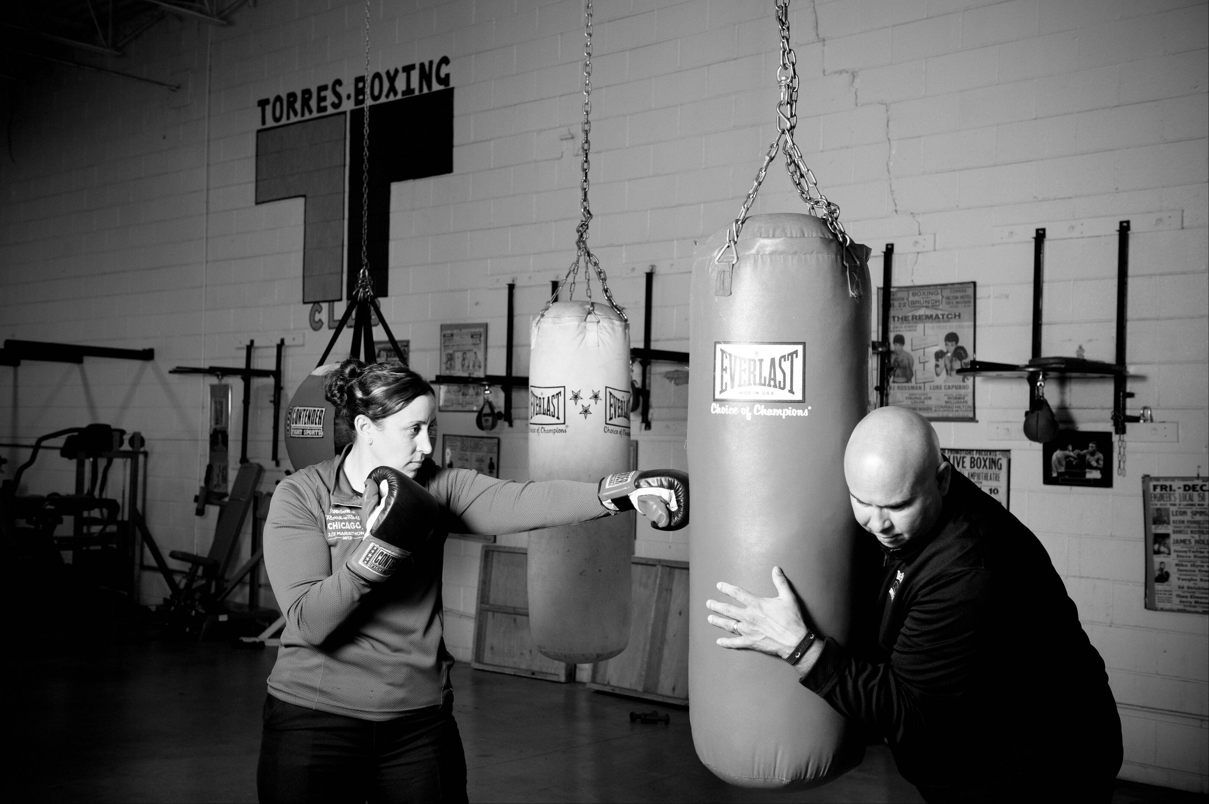 "Elgin Police Cmdr. Ana Lalley trains with Aurora Police Sgt. Alfredo Dean at the Jesse ""The Law"" Torres Boxing Club in Aurora."