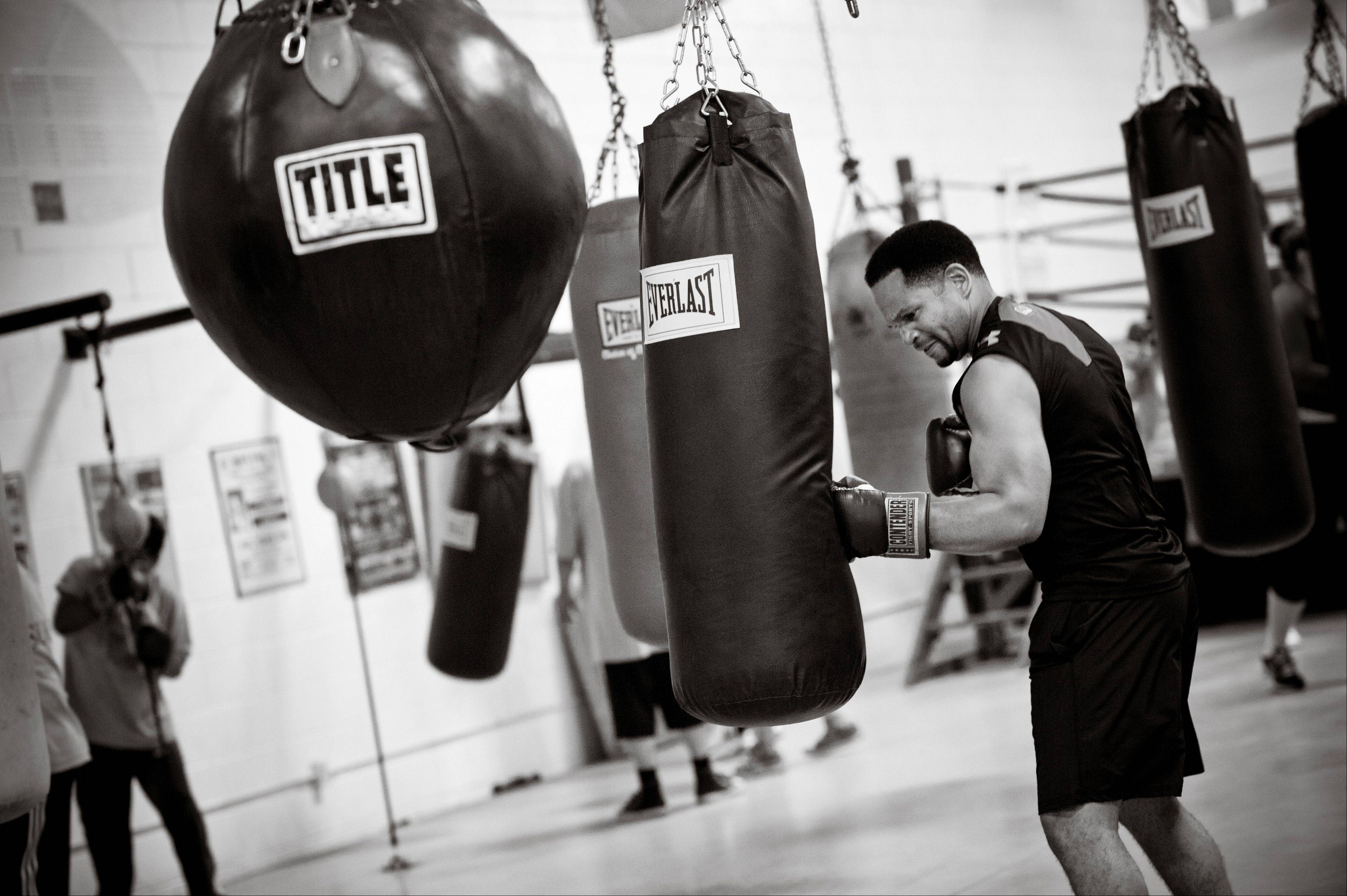 "Aurora alderman and defense attorney Richard Irvin works the heavy bag while training at the Jesse ""The Law"" Torres Boxing Club in Aurora."