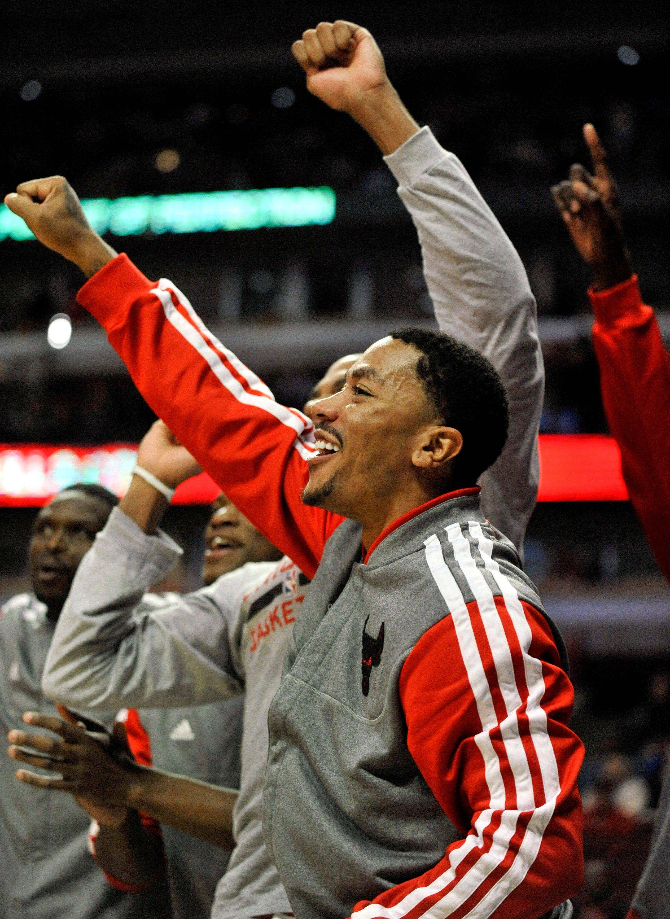 Derrick Rose celebrates while on the bench during the final minutes of a preseason win over Milwaukee on Monday night at the United Center.