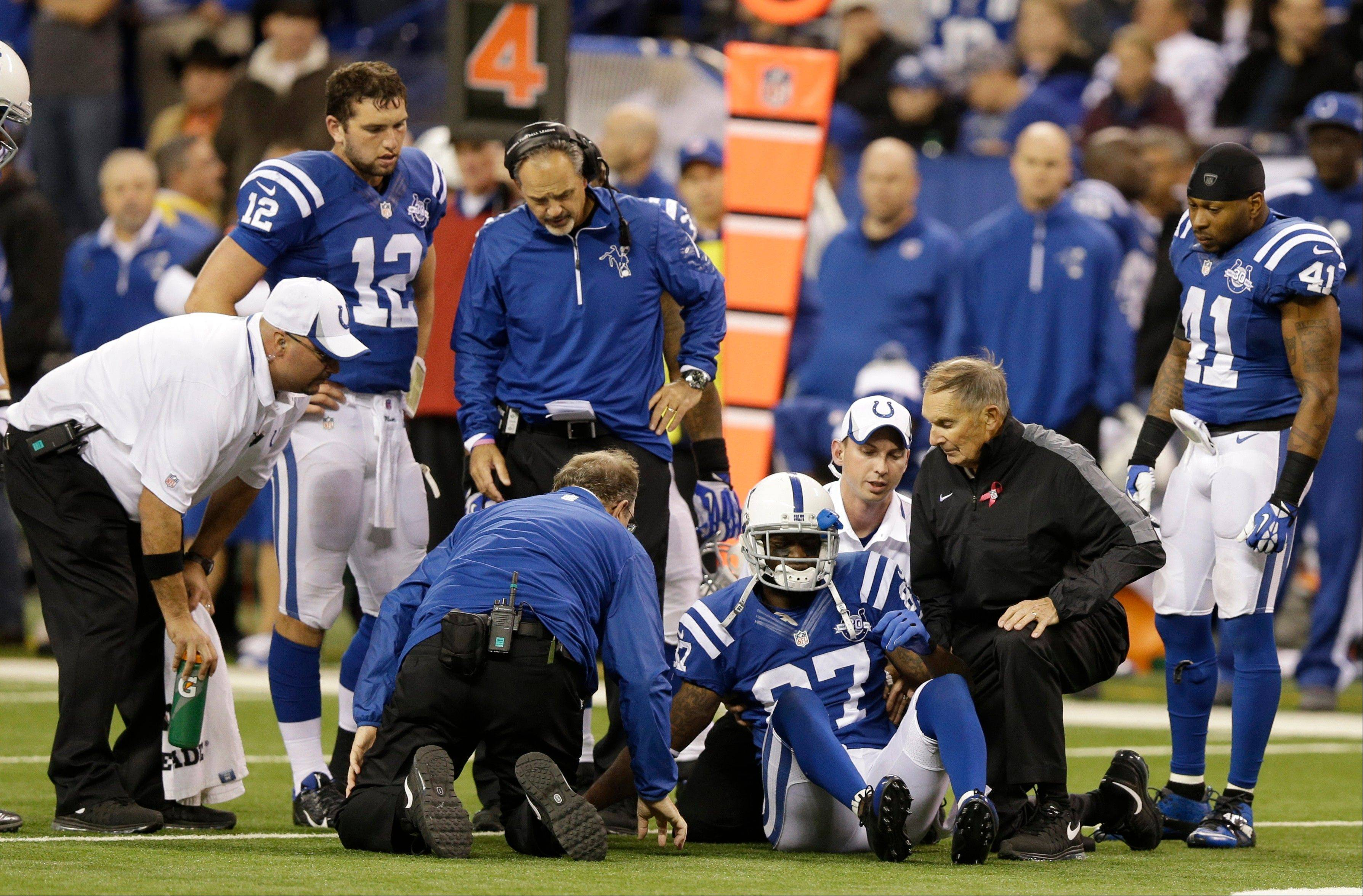 Indianapolis Colts wide receiver Reggie Wayne talks to trainers as they tend to his injured knee during the second half of Sunday's home game against Denver.