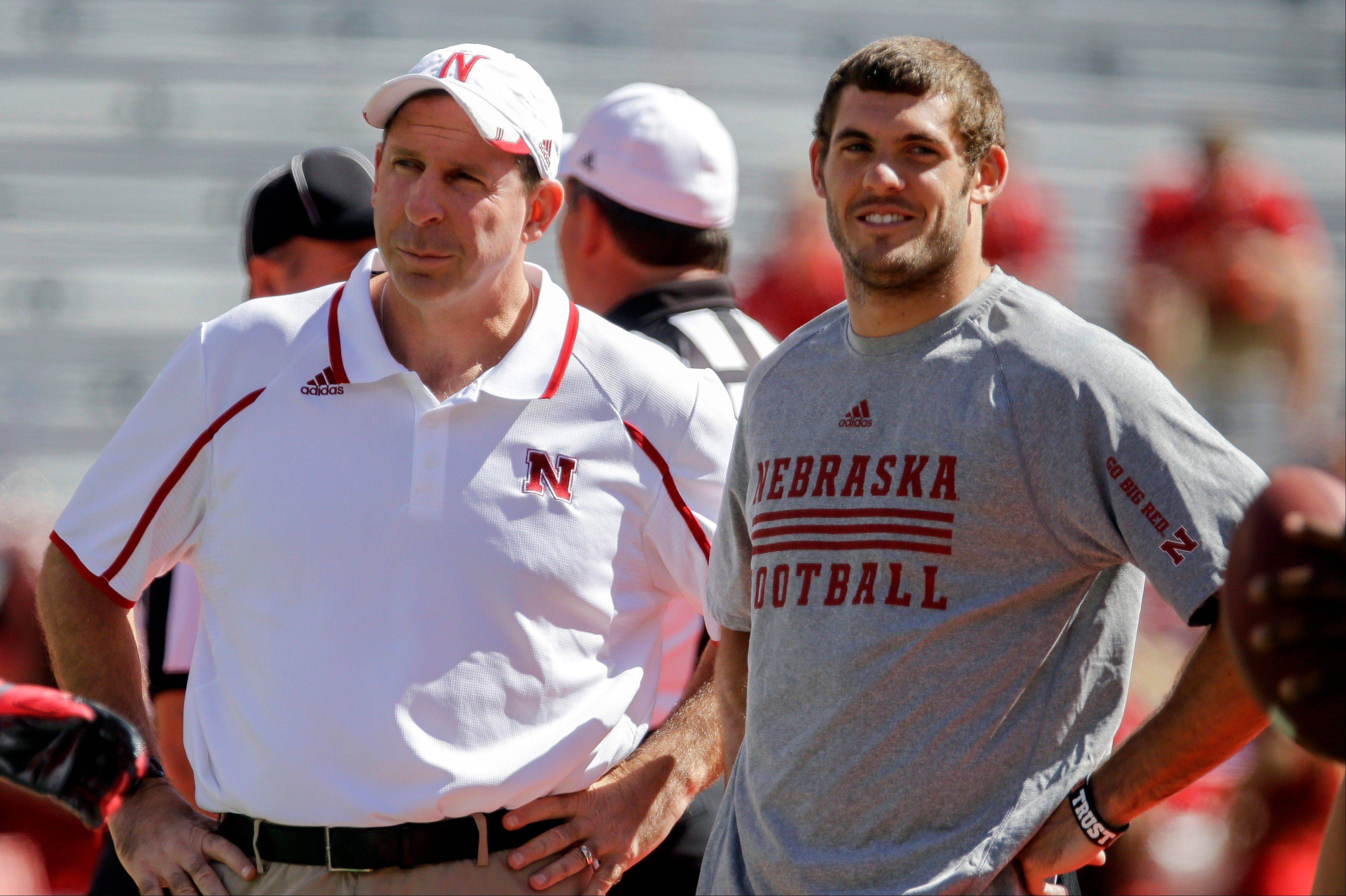 Nebraska head coach Bo Pelini, left, and injured Nebraska quarterback Taylor Martinez watch the team before a Sept. 21 game against South Dakota State. Martinez could play against Minnesota this Saturday if he's able to put more stress on his injured left foot as the week progresses.