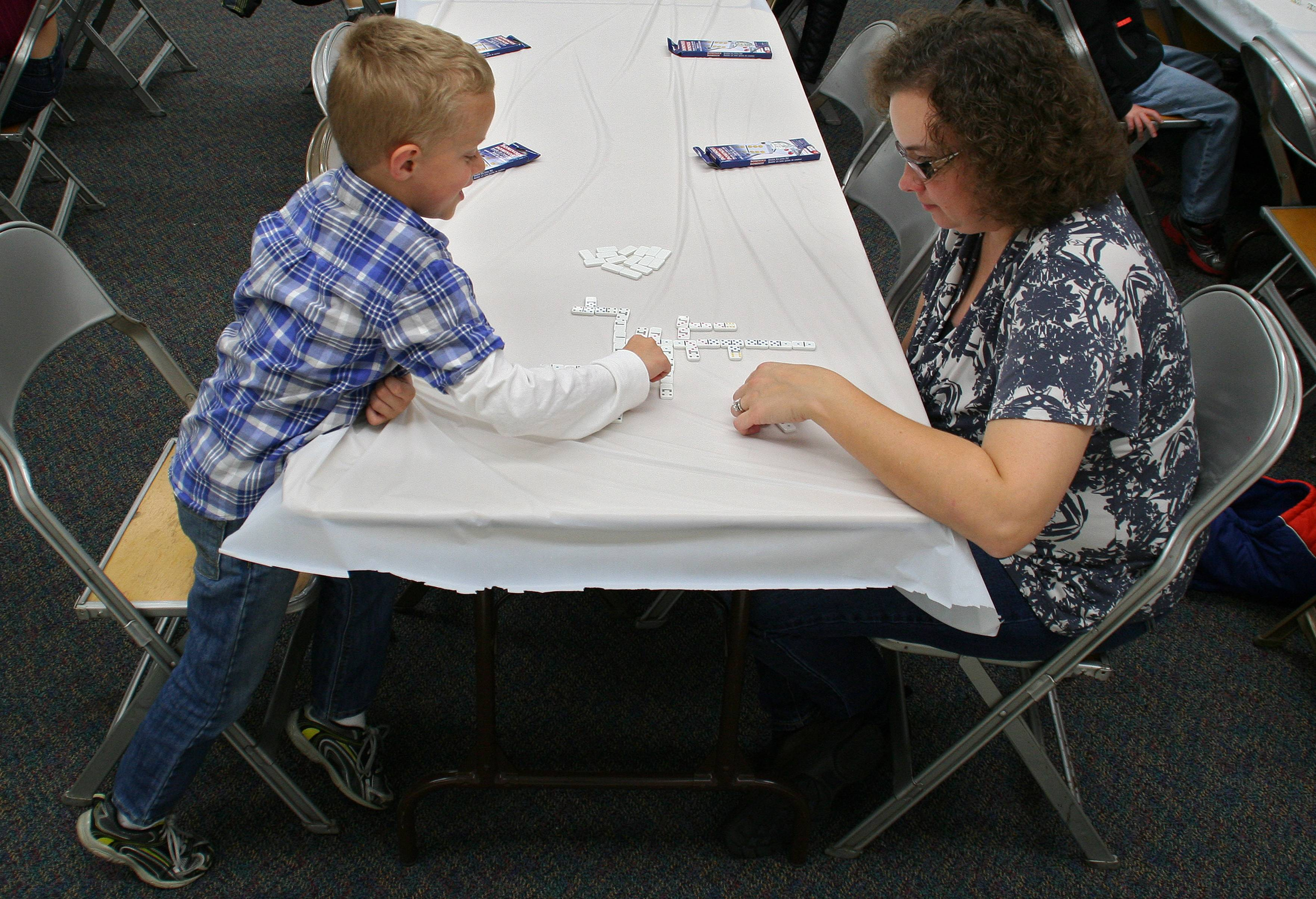 Christian Bardygula, and his mom, Dawn, play dominoes at the Mother and Son Dominoes and Pizza Event on October 19.