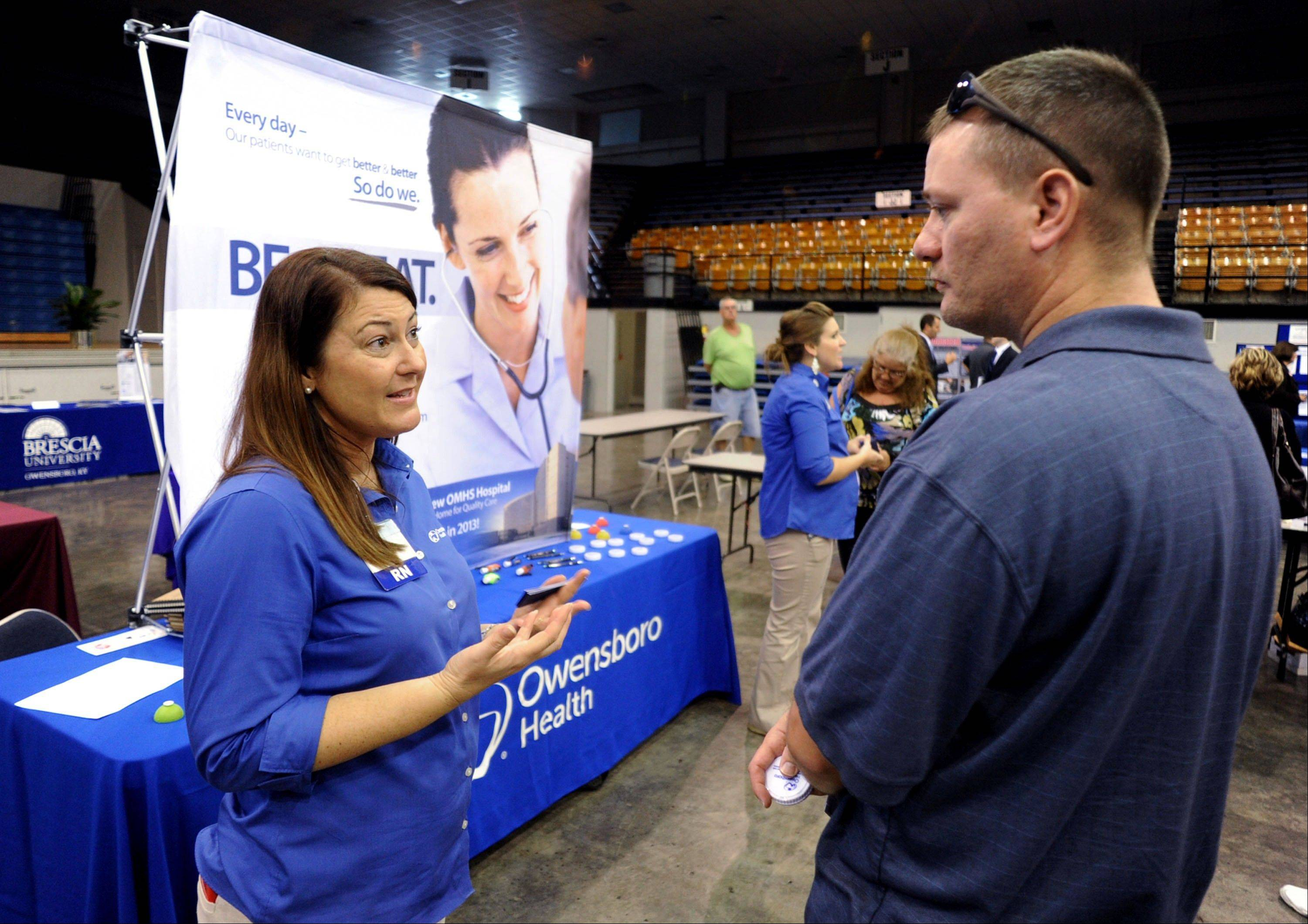 Registered nurse Salanda Bowman, left, talks with part-time Kentucky Wesleyan College student Jason Ward, of Whitesville, about job openings at the Owensboro Health Regional Hospital during a Regional Career and Job Fair in the Owensboro Sports Center in Owensboro, Ky.