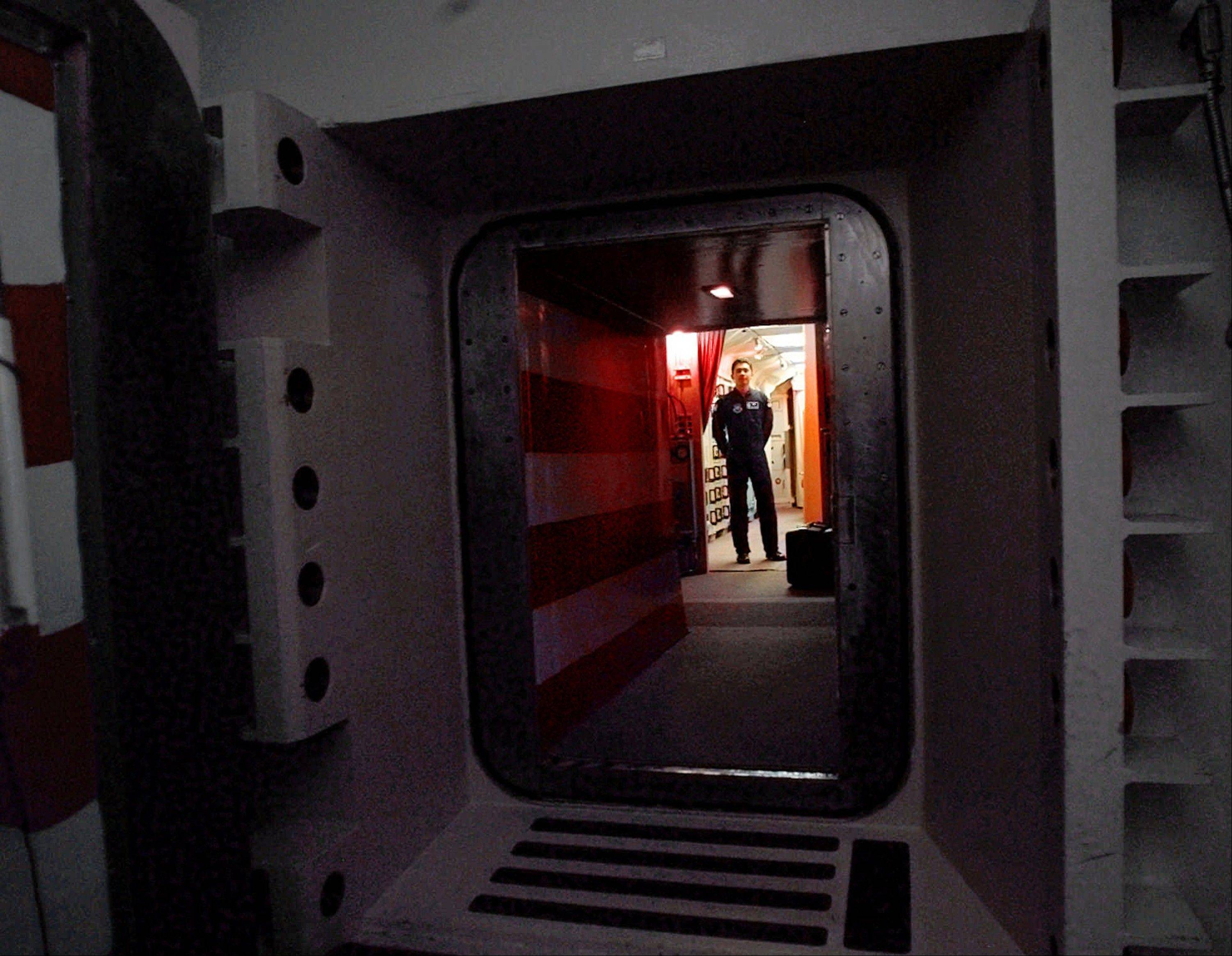 An Air Force missile crew commander stand at the door of his launch capsule 100-feet underground, where he and his partner are responsible for 10 nuclear-armed ICBM's, in north-central Colorado.
