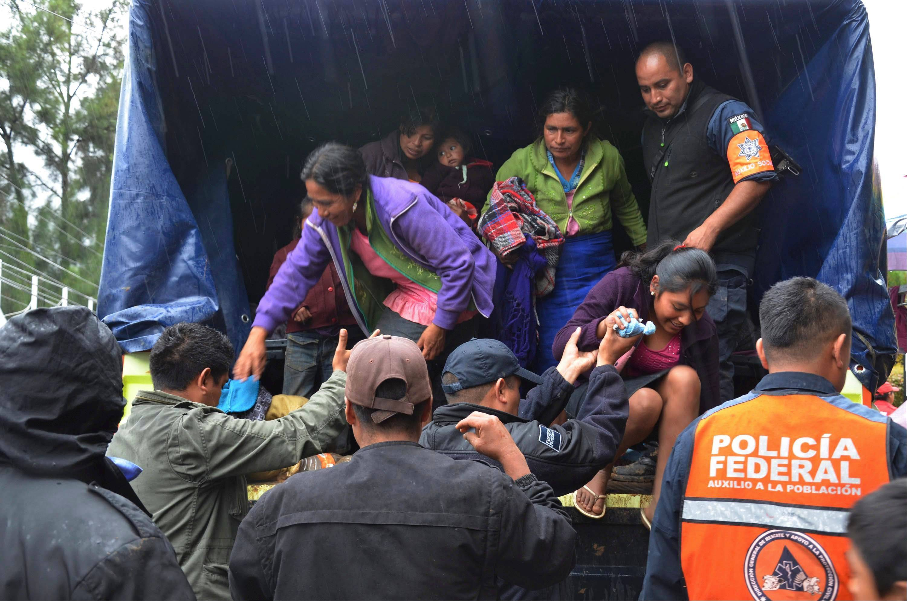 People are helped by federal police as they get off a truck to be taken to as makeshift shelter in the city of Chilpancingo, Mexico, Monday Oct. 21, 2013. At least 120 families from nearby communities were evacuated when Hurricane Raymond gained more strength and threatened to hurl heavy rains onto a sodden region already devastated by last month's Tropical Storm Manuel. (AP Photo/Alejandrino Gonzalez)