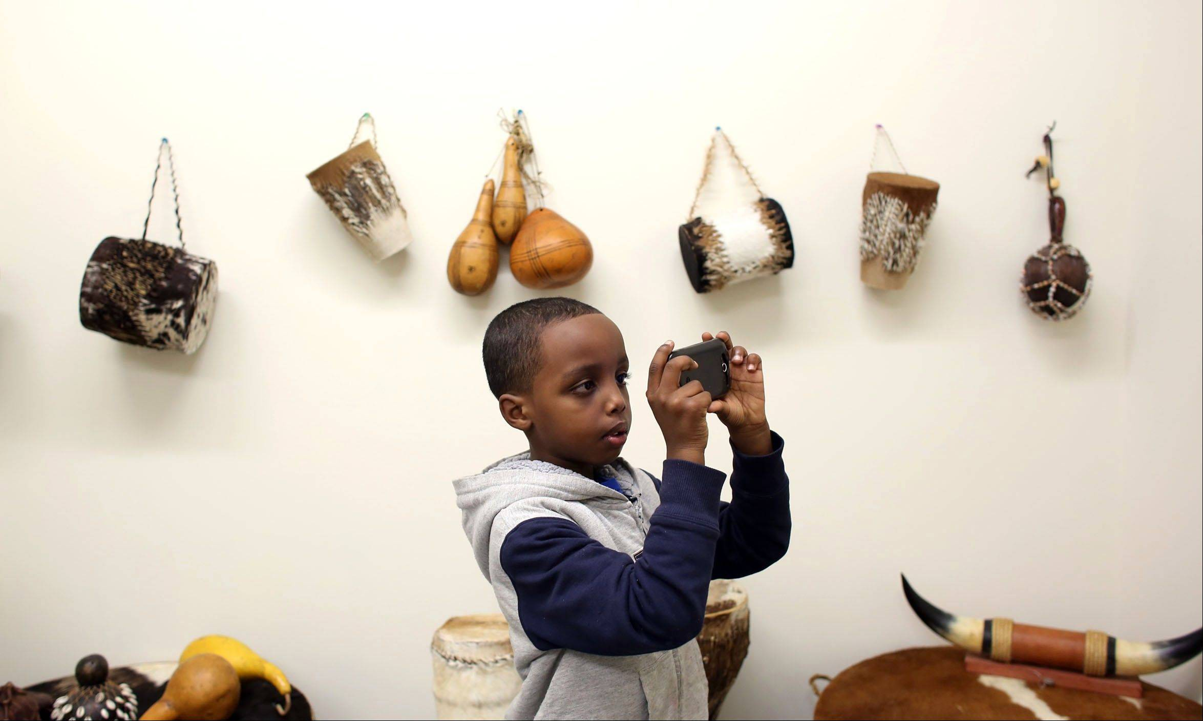 Suber Aden, 6, of St. Paul, takes pictures of traditional Somali instruments during the grand opening of the Somali Artifact and Cultural Museum in Minneapolis Saturday.