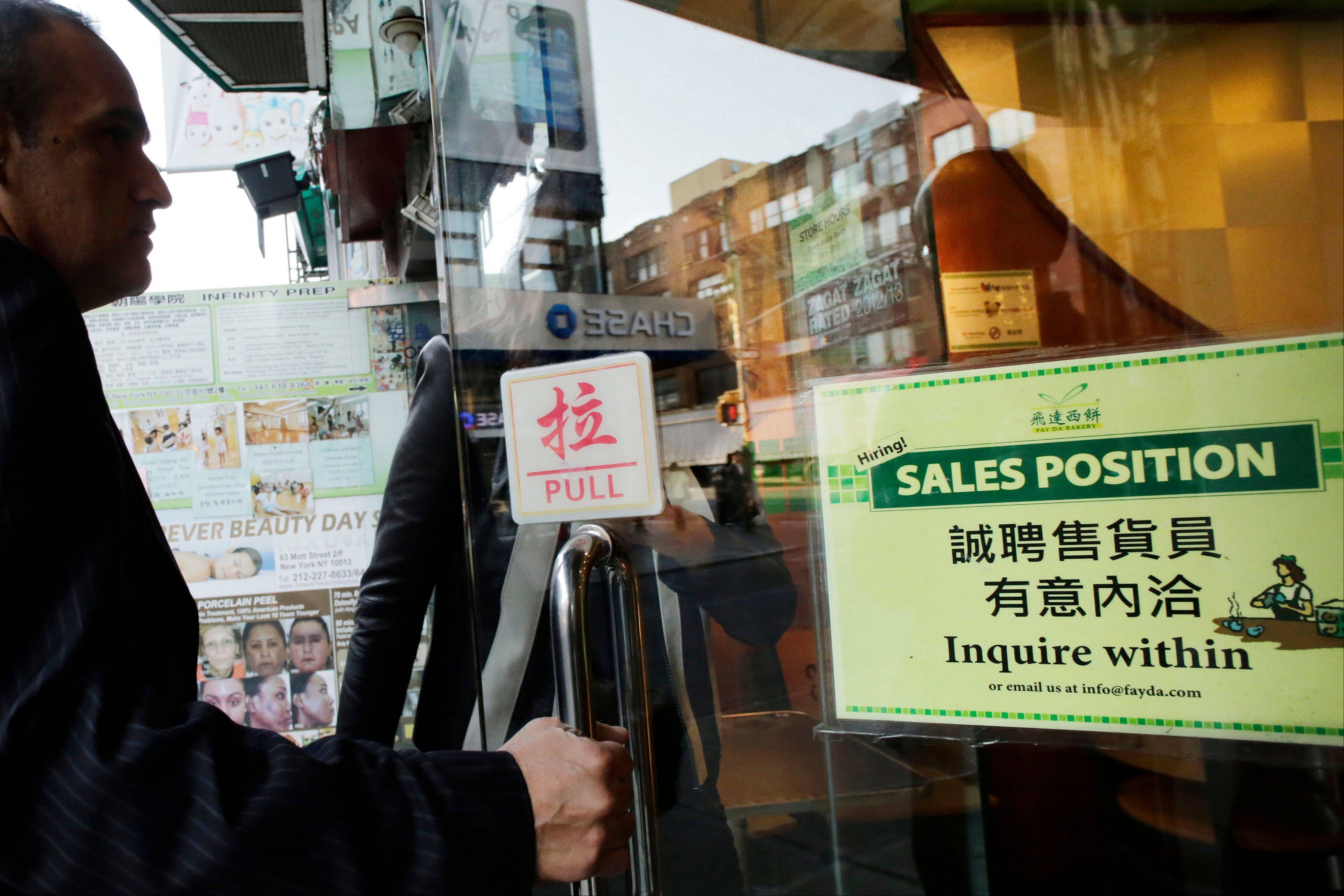 "A customer enters a Chinese bakery that has a sign posted in the door, ""Hiring! Sales Position Inquire within,"" Tuesday in New York. The U.S. economy added just 148,000 jobs in September, suggesting that employers held back on hiring before a 16-day partial government shutdown began Oct. 1."