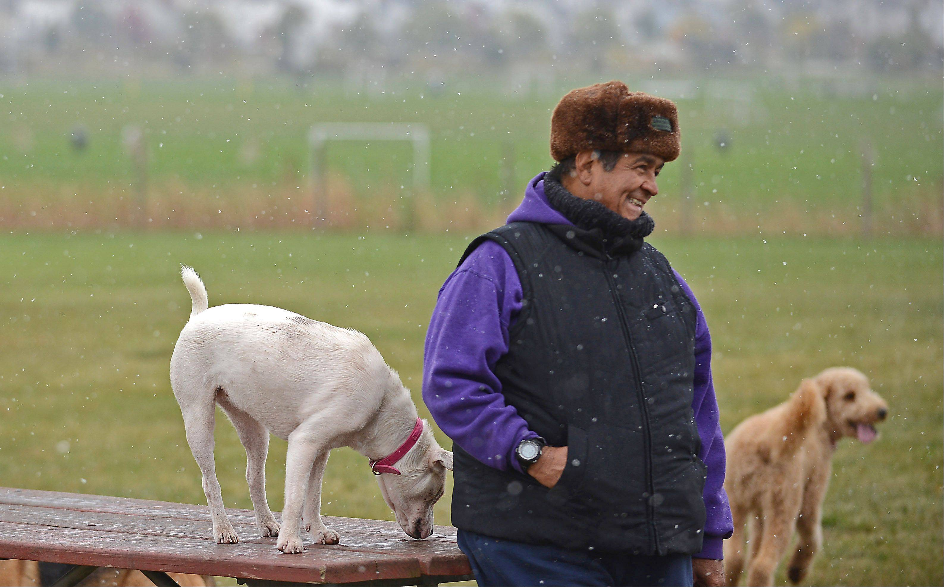 Manny Galvan of St. Charles smiles while talking to some of the other regulars at the dog park as the snow falls at James O. Breen Community Park Tuesday. He brought his dog Mimsy, not pictured, along.