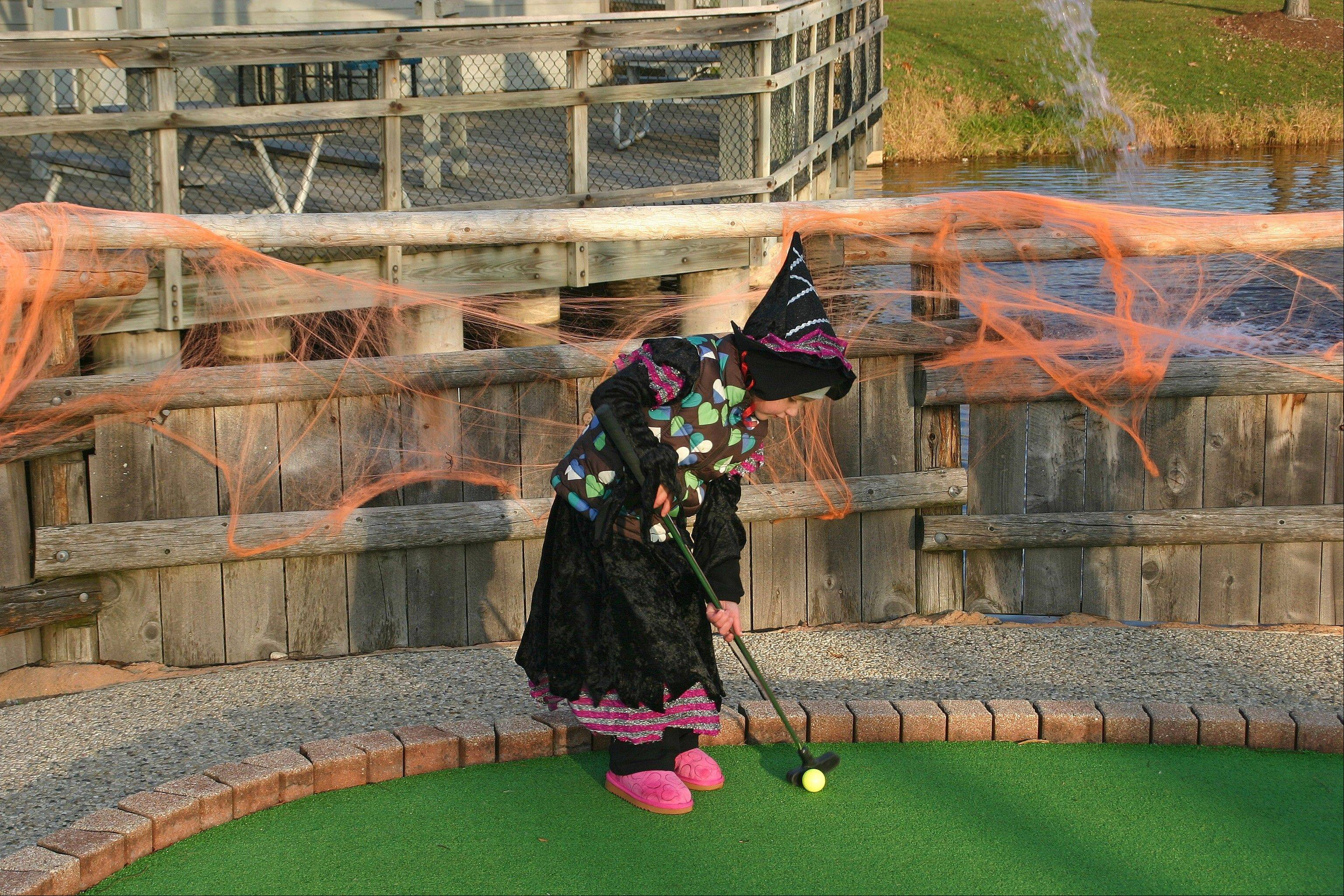 A tiny witch shoots for par at Mountain View Adventure Center during the 2012 Haunted Hole-O-Ween.