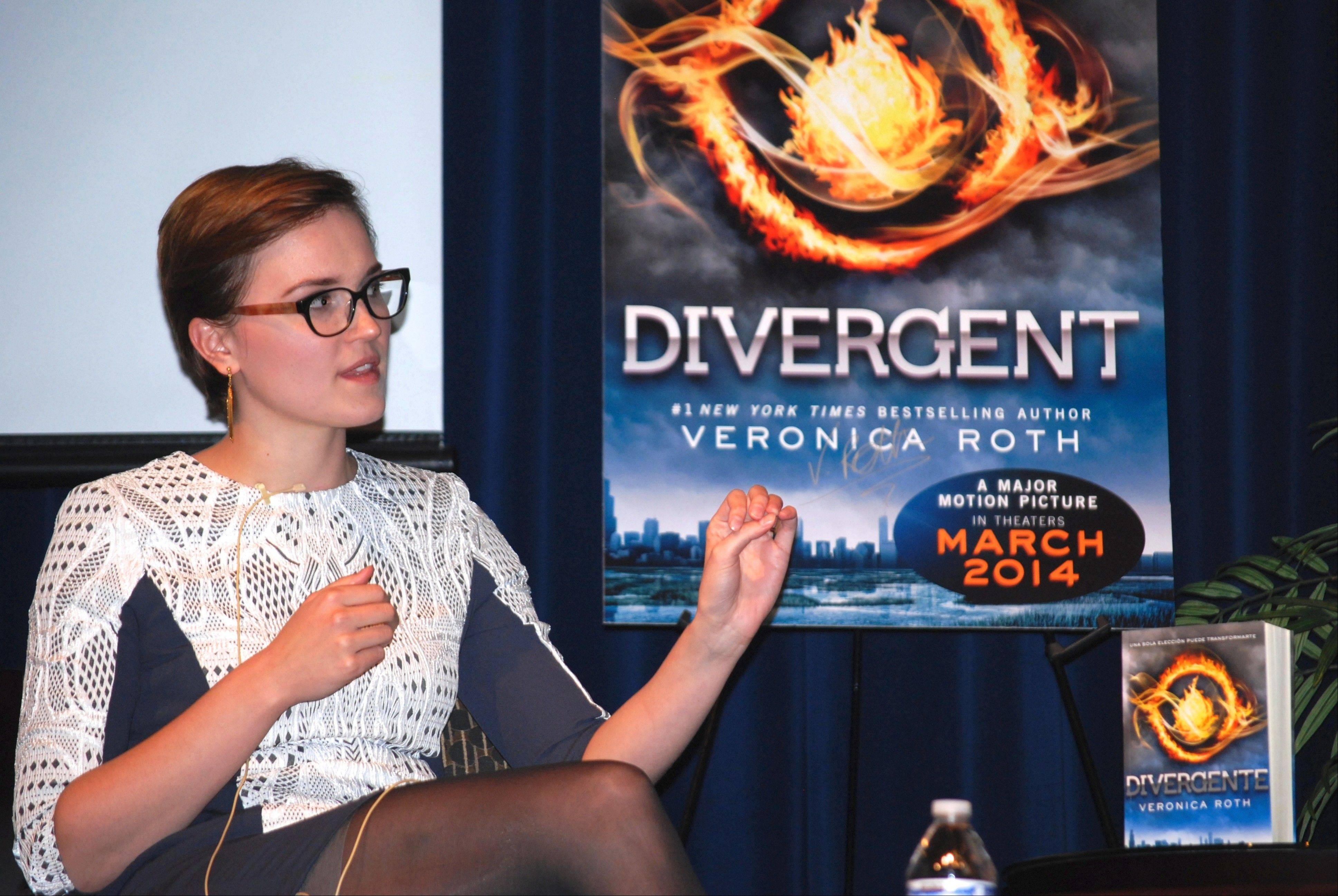 "Sitting in front of a poster for the movie based on her debut novel, ""Divergent"" author Veronica Roth speaks at Barrington High School, where the best-selling author graduated in 2006."