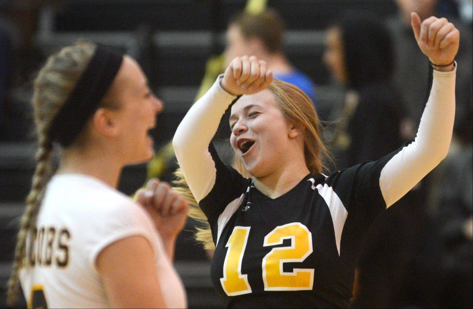 Jacobs' Mackie Traub, right, celebrates with teammate Kassie Kasper Tuesday night at Jacobs. Traub was celebrated as the lone senior team member on senior night for the Golden Eagles, who swept the Chargers in two sets.