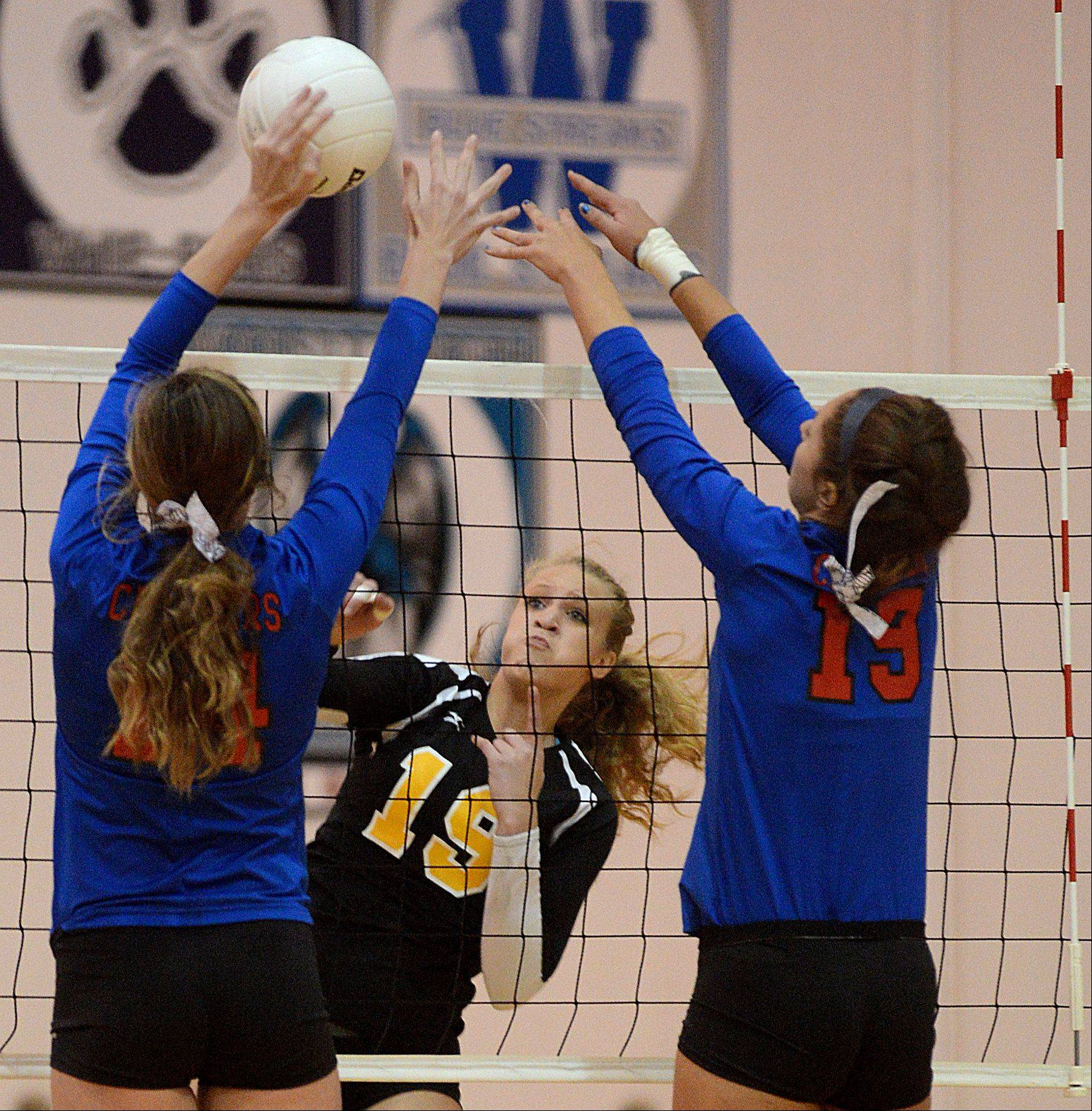 Dundee-Crown's Emily Michalski, left, and Ashley Raby, right, try to block Jacobs' Kyla Fitzsimmons, center, during a varsity volleyball game at Algonquin on Tuesday night.