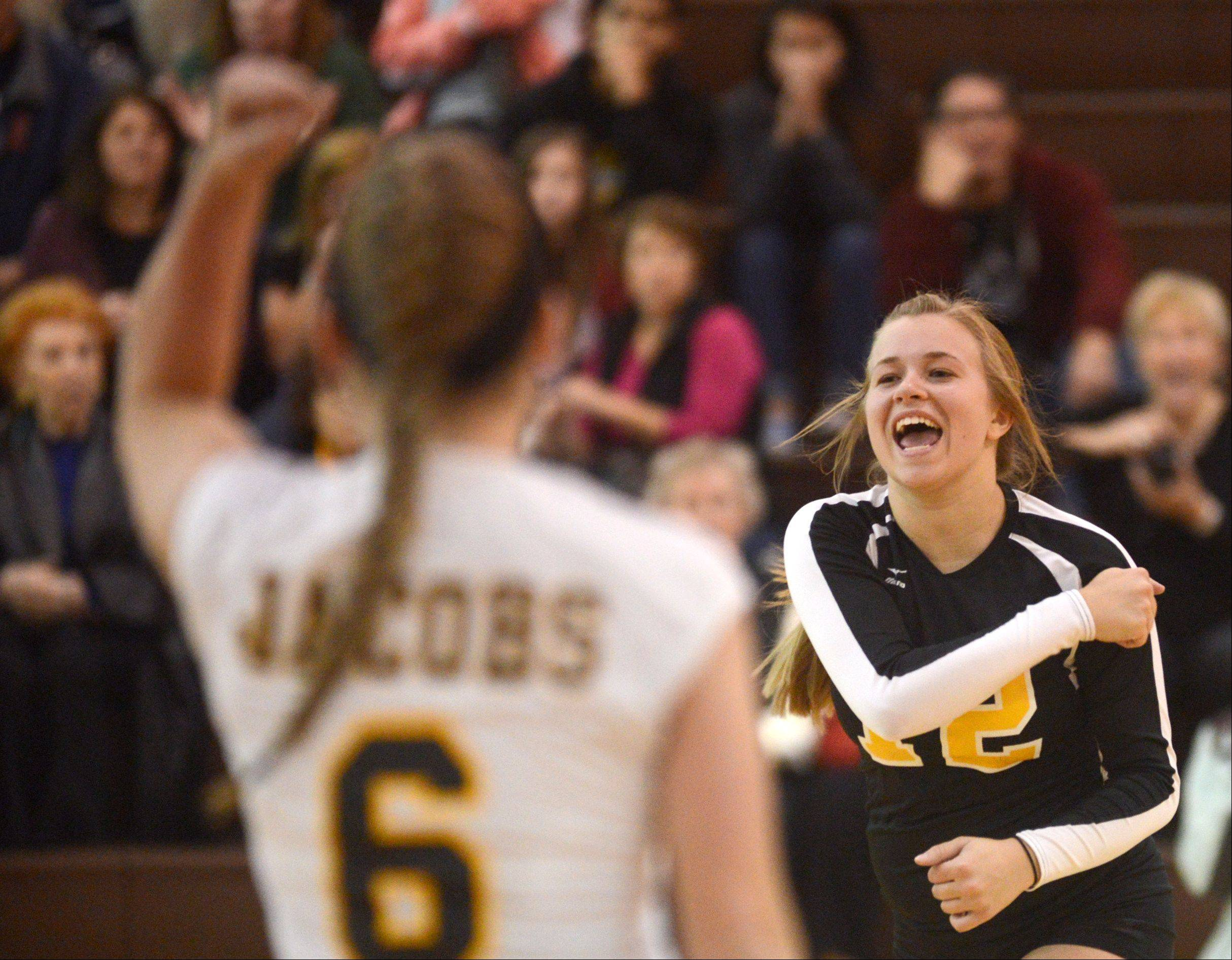 Jacobs' Mackie Traub, right, celebrates with teammate Kassie Kasper, left, during a varsity volleyball game against Dundee-Crown at Algonquin on Tuesday night. Traub was celebrated as the lone senior team member on senior night for the Golden Eagles.
