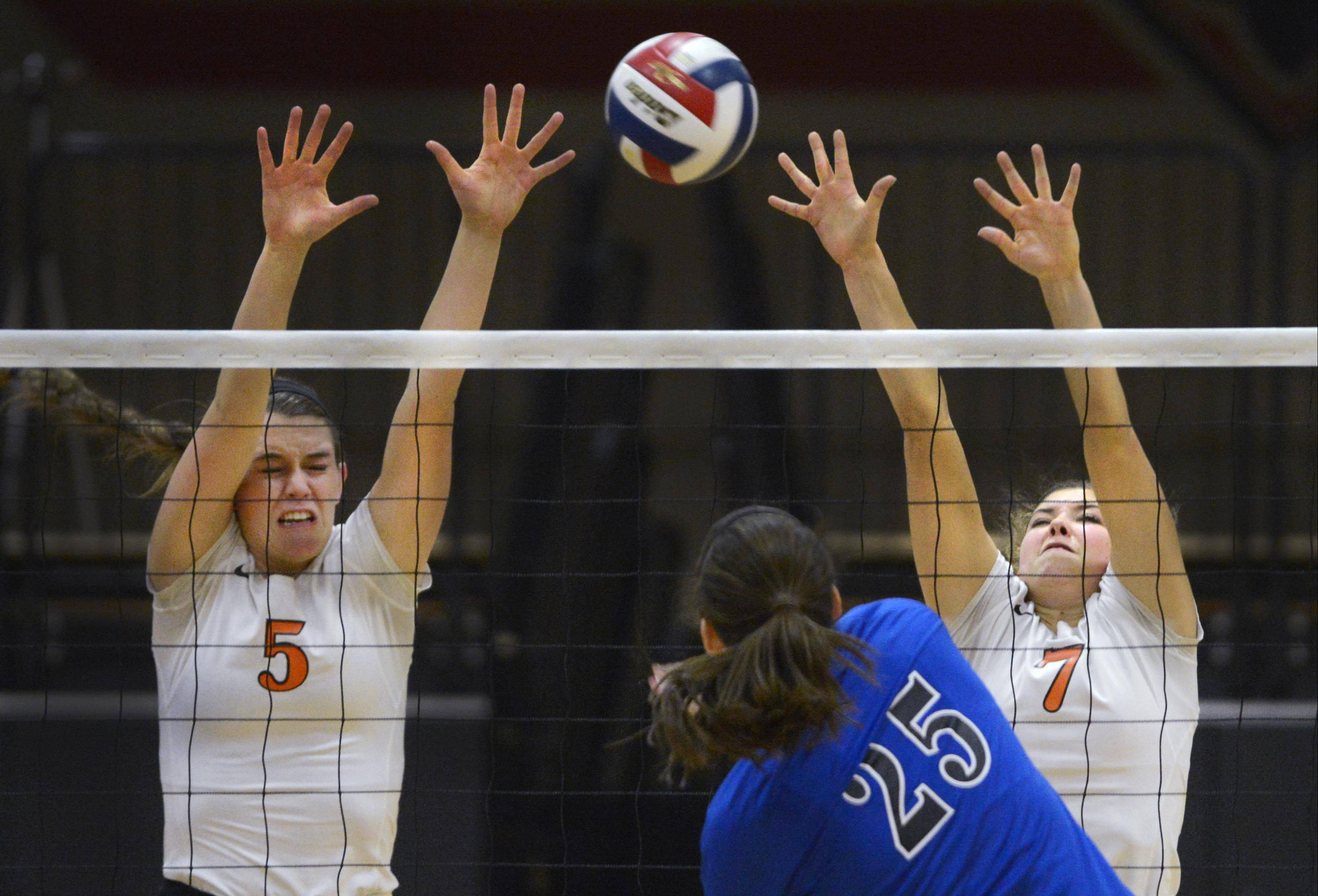 Geneva's Ally Barrett hits against St. Charles East's Alex Mazanke and Meagan Smith, right, Tuesday in St. Charles.