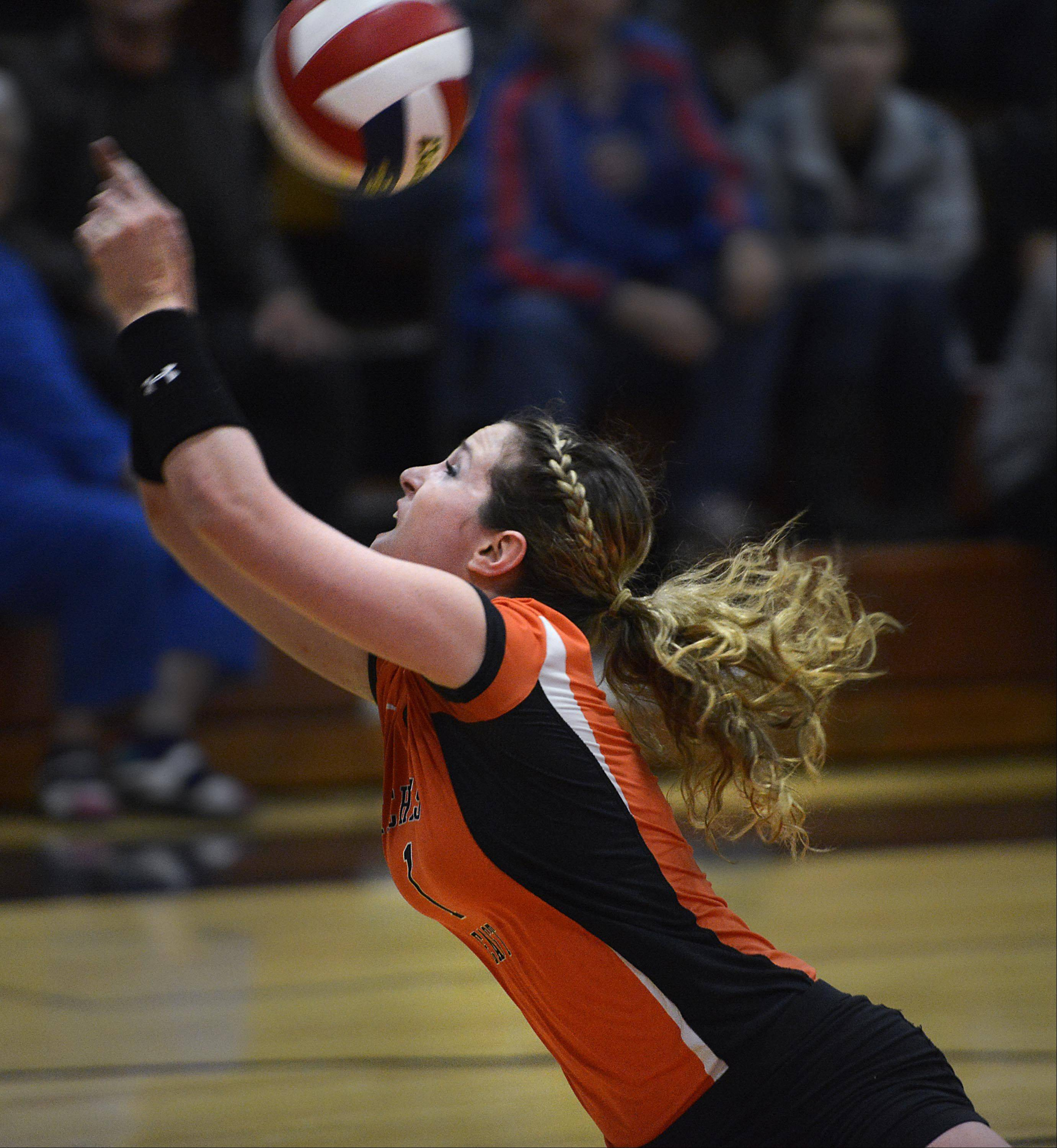 St. Charles East's Anne Hughes runs away from the net to reach a deflected shot by Geneva Tuesday in St. Charles.
