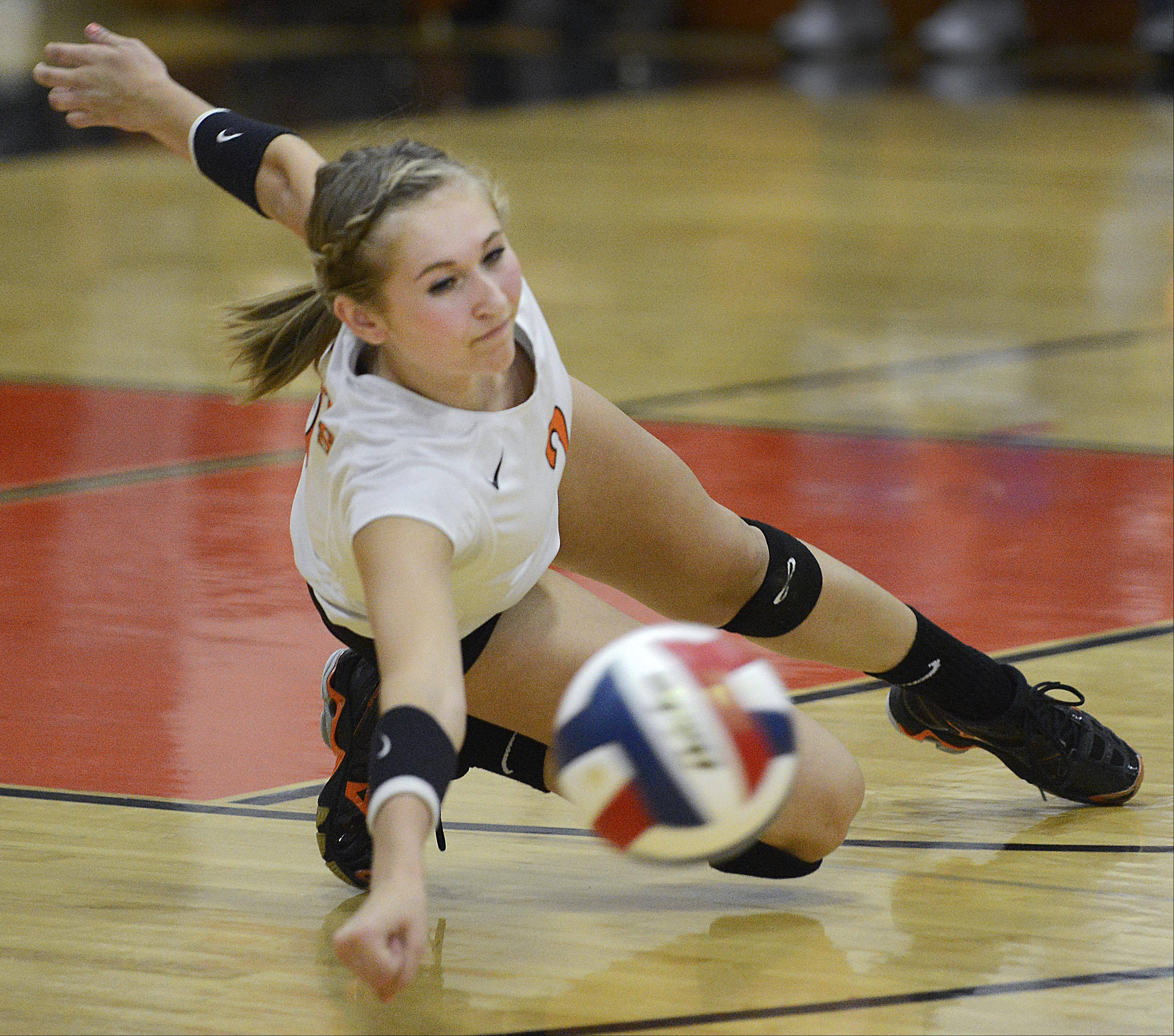 St. Charles East's Emily Vitel falls sideways to reach a hit by Geneva Tuesday in St. Charles.