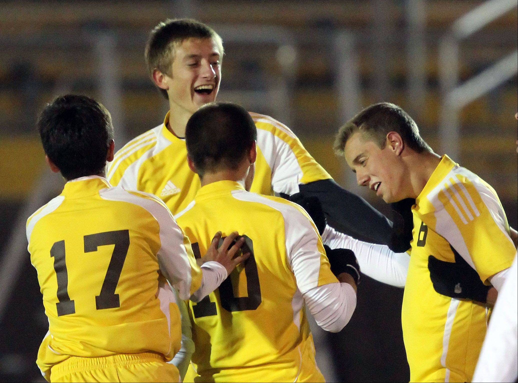 Carmel teammates celebrate with Evan Potter (6), right, after his first-half goal during regional semifinal action against St. Viator Tuesday night at Carmel Catholic High School.