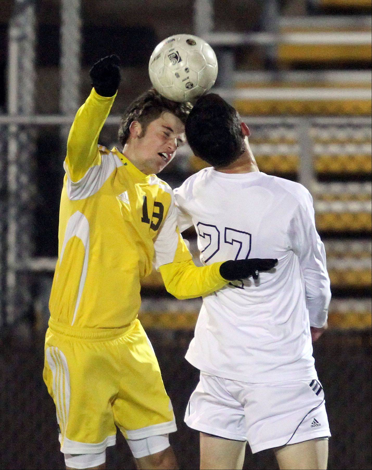 Carmel's Ryan McKernan, left, and St. Viator's Nick Winter go up for a header during regional semifinal action Tuesday night at Carmel Catholic High School.