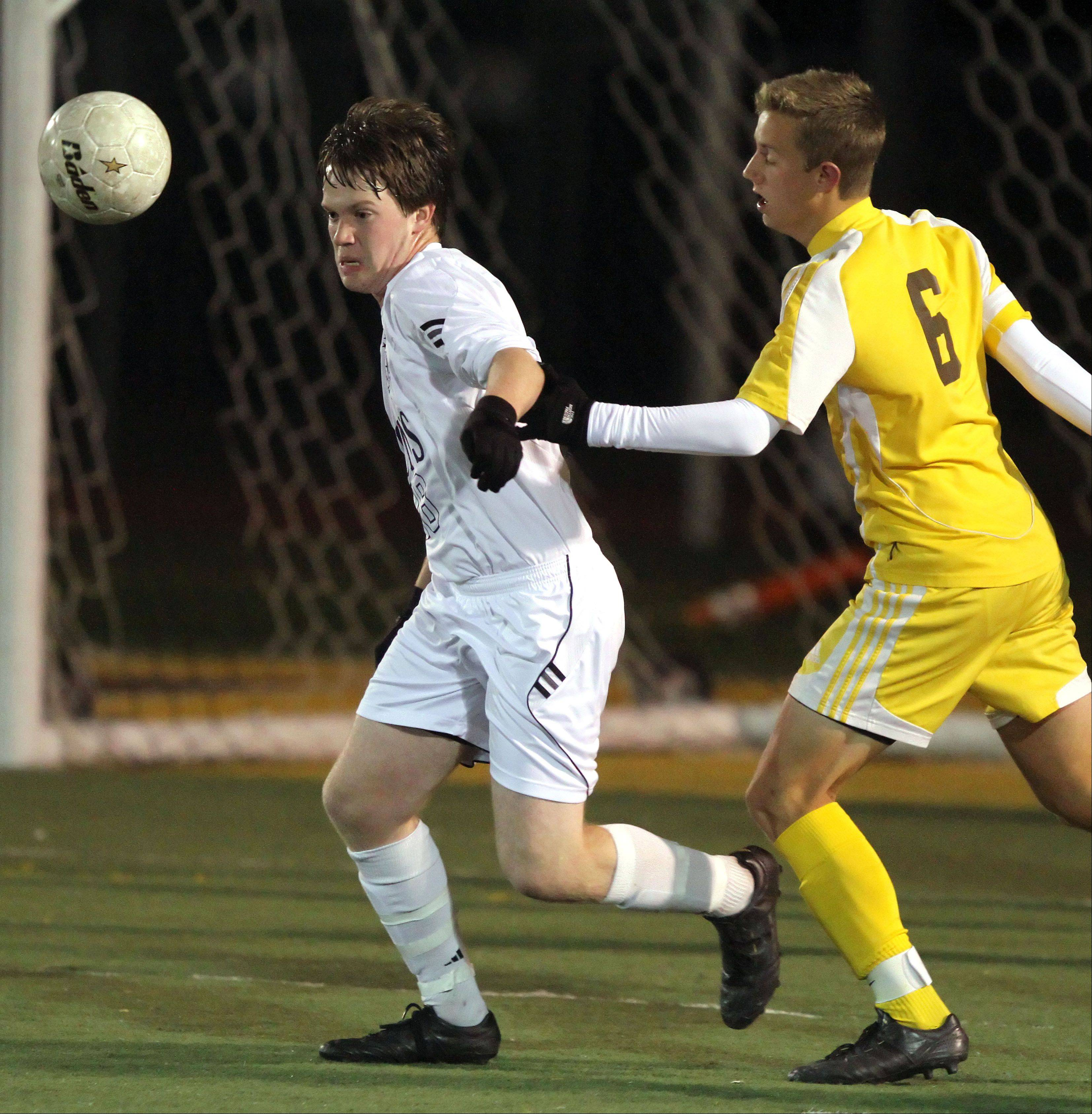 St. Viator's Kevin McMahon, left, and Carmel's Evan Potter battle for the ball during regional semifinal action Tuesday night at Carmel Catholic High School.