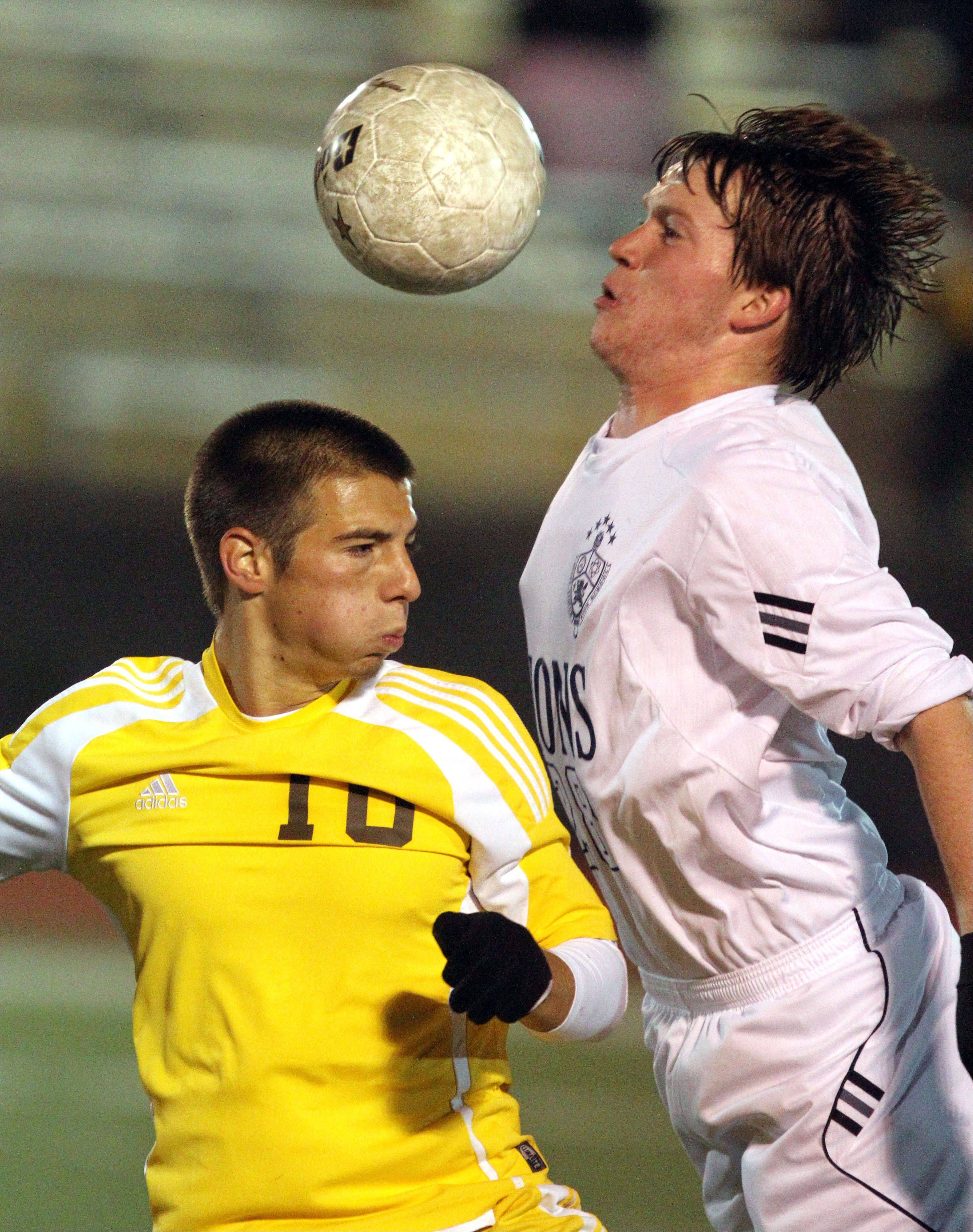 Carmel's Adam Cloe, left, and St. Viator's Kevin McMahon go up for a header during regional semifinal action Tuesday night at Carmel Catholic High School.