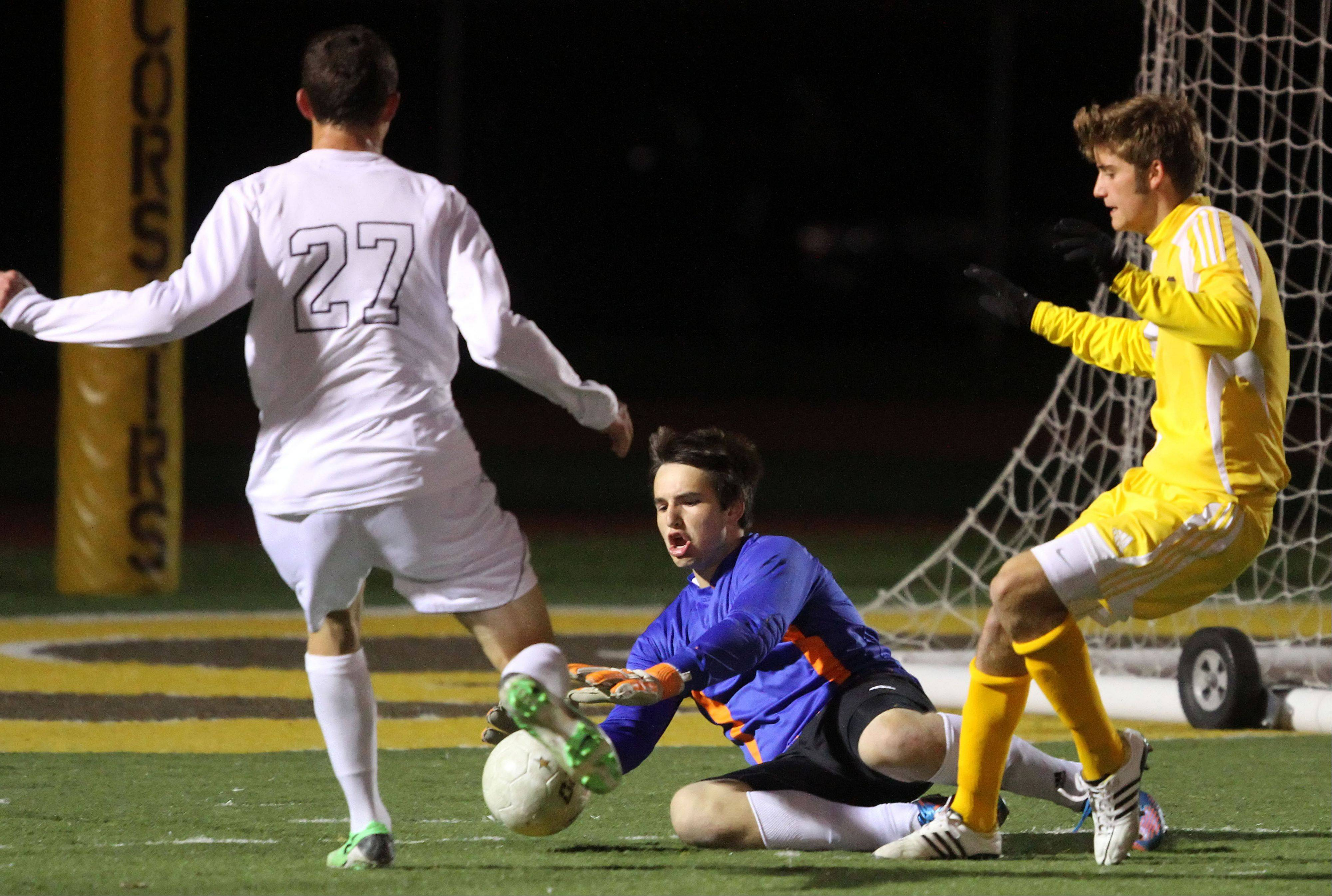 Carmel goalie Jacob Spheeris makes a save on St. Viator's Nick Winter as Carmel's Ryan McKernan trails during regional semifinal action Tuesday night at Carmel Catholic High School.